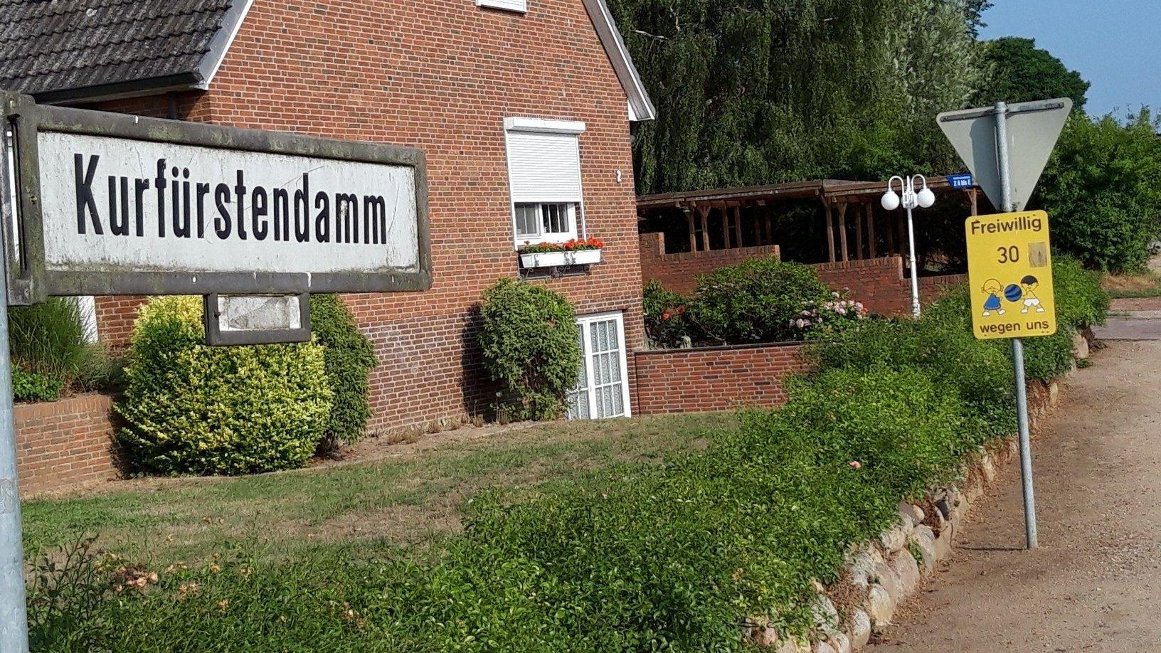 """Straßenschild """"Kurfürstendamm"""" vor einem Dorfhaus und Sandweg in Berlin/Schleswig-Holstein."""