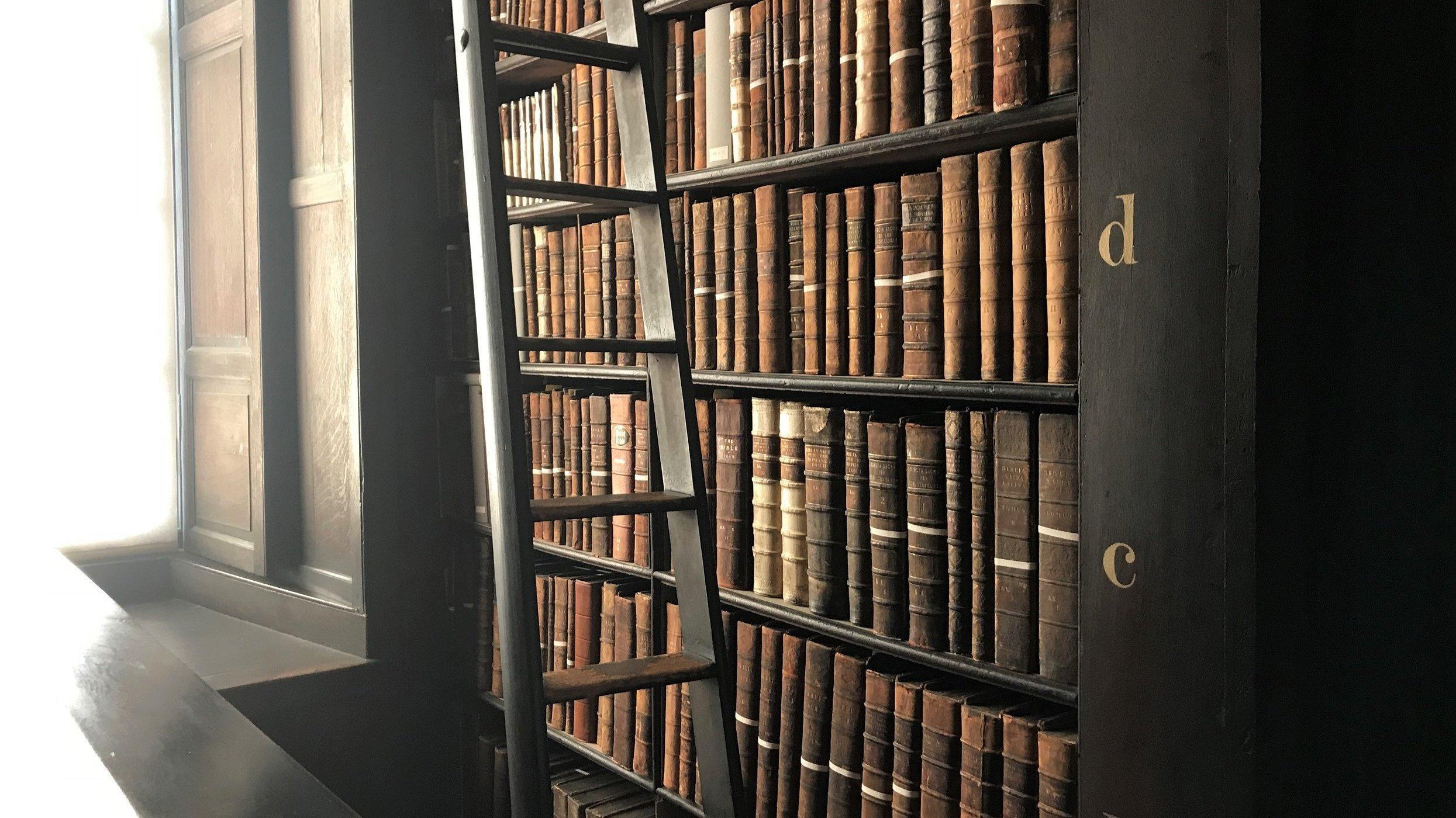 Ein Regal mit vielen alten Büchern der Bibliothek des Trinity College in Dublin, am Rand eine Leiter.
