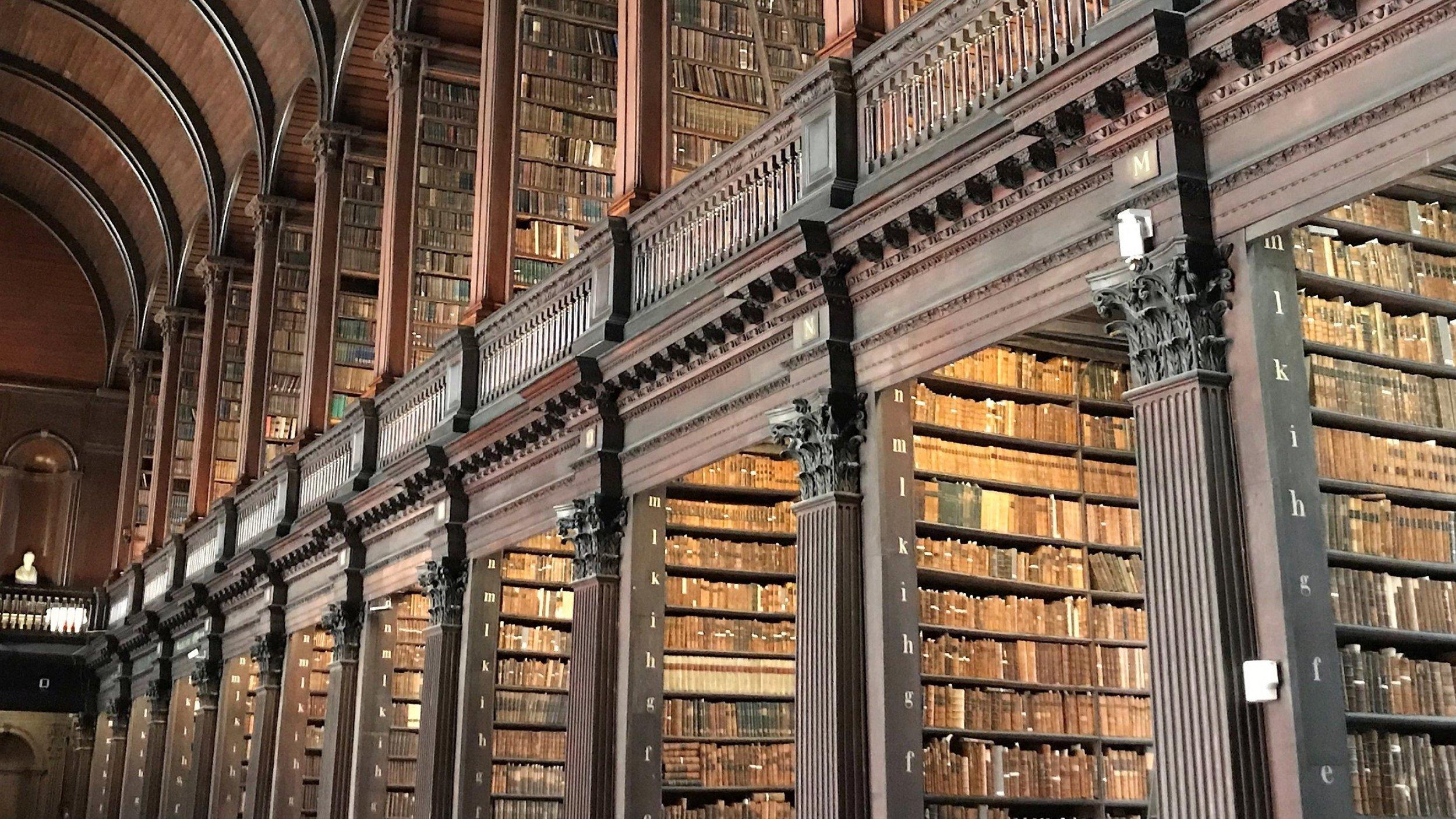 Ein hoher Saal mit zahlreichen Bücherregalen, gefüllt mit kostbaren Büchern. Das Trinity College in Dublin hat eine der ehrwürdigsten Bibliotheken der Welt.