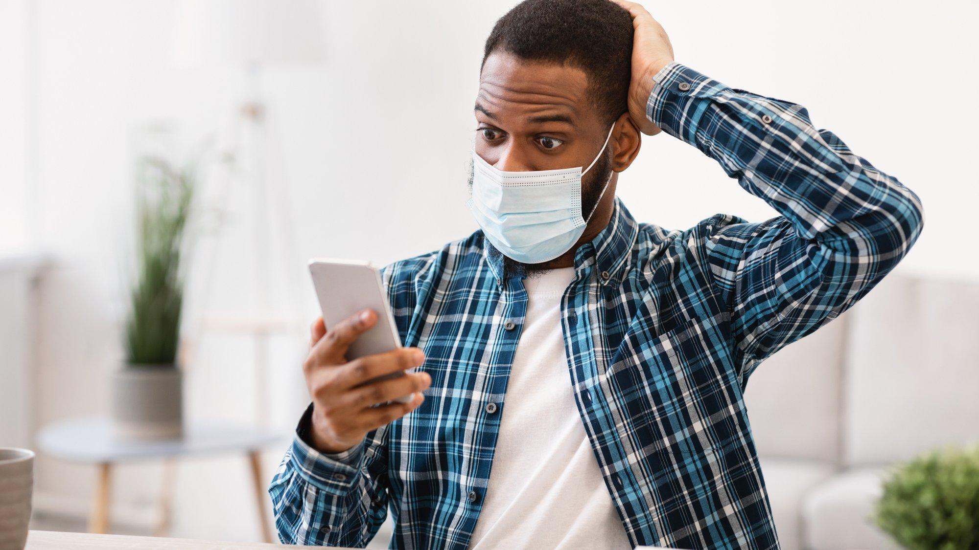 Ein Mann liest Nachrichten auf dem Handy und blickt dabei besorgt.