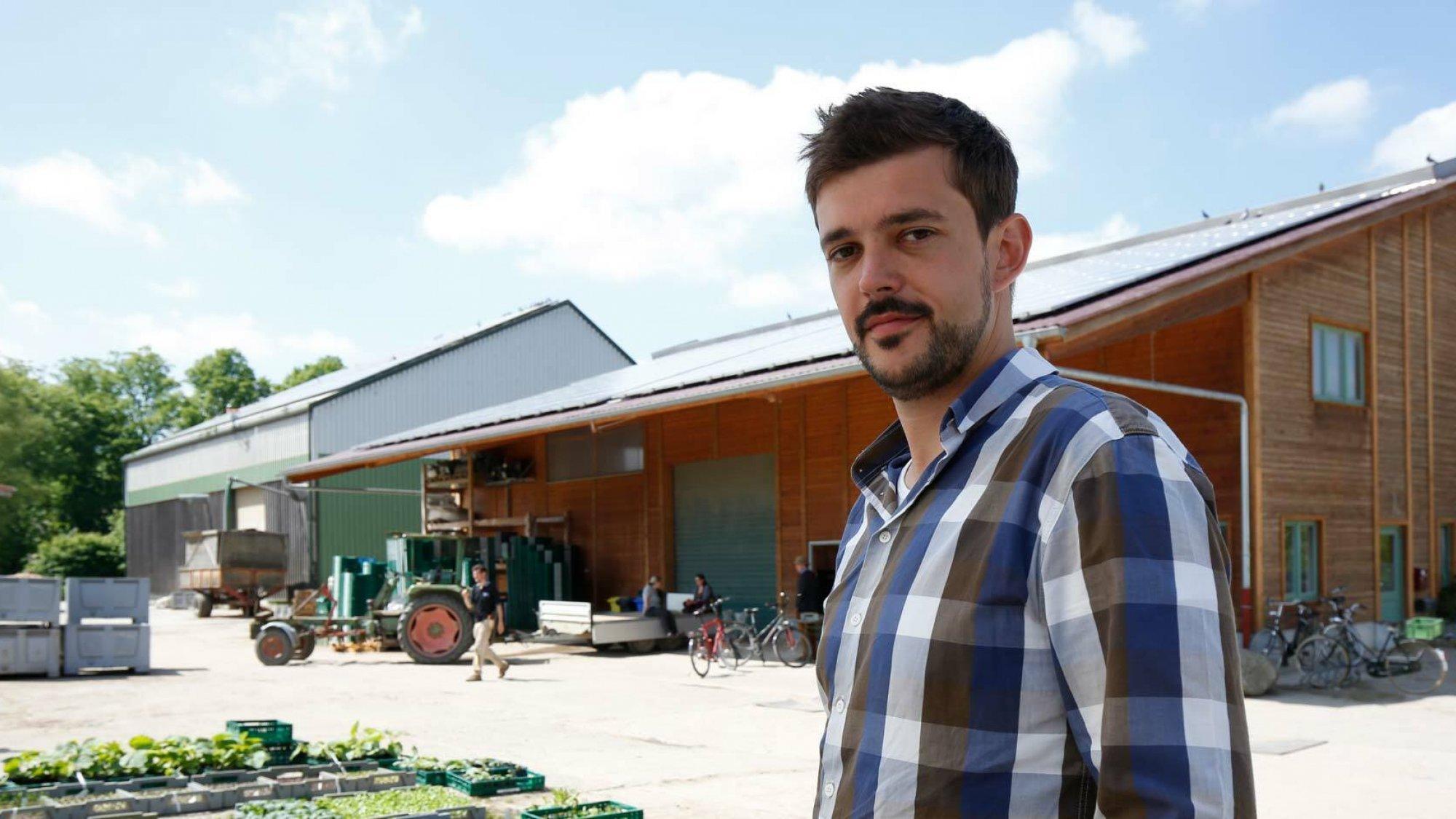 Ein Mann steht auf seinem Bauernhof. Im Hintergrund wird Gemüse in Kisten gefüllt.