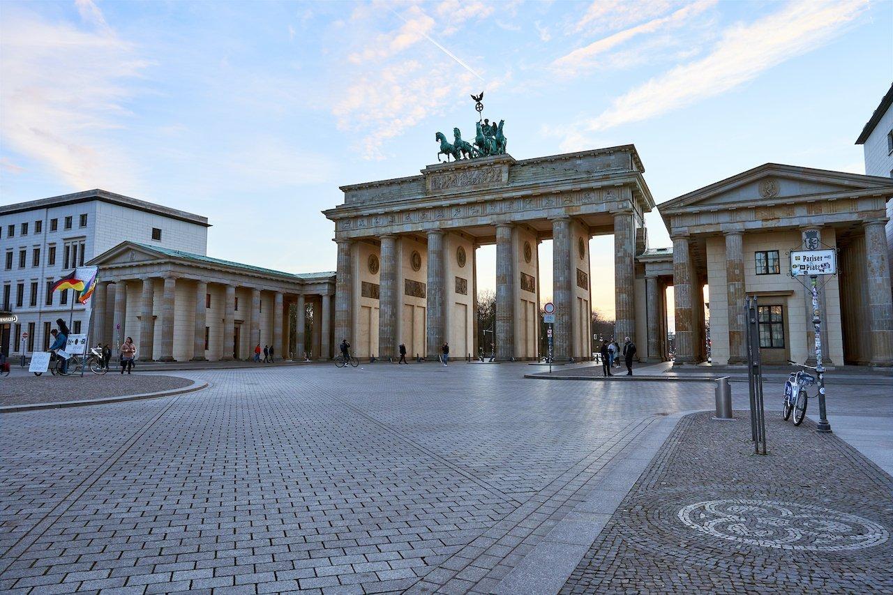 Das Bild zeigt das Brandenburger Tor. Der Vorplatz ist fast ganz leer. Rechts steht ein angeschlossenes Fahrrad an einem Straßenschild.