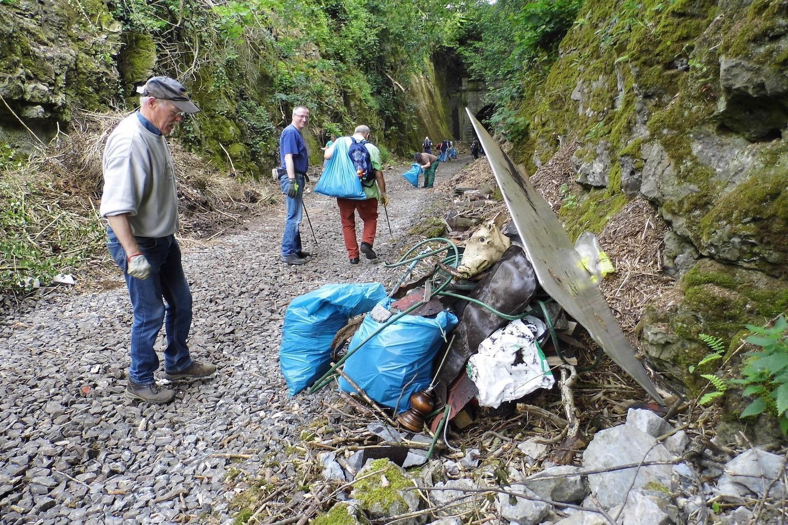 Vier ältere Menschen laufen entlang eines steinigen Weges und sammeln in blauen Säcken den Müll vom Wegesrand.