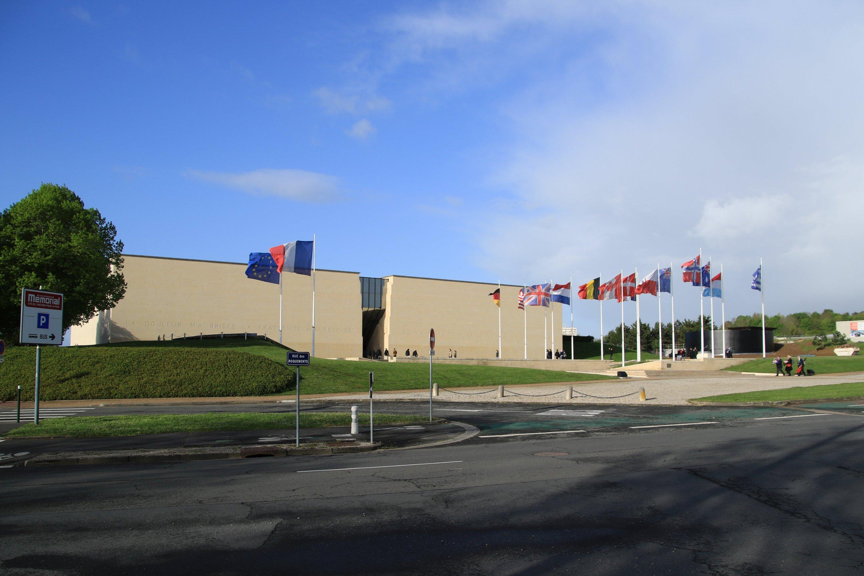 Ein Museumsgebäude von außen mit Flaggen verschiedener Nationen
