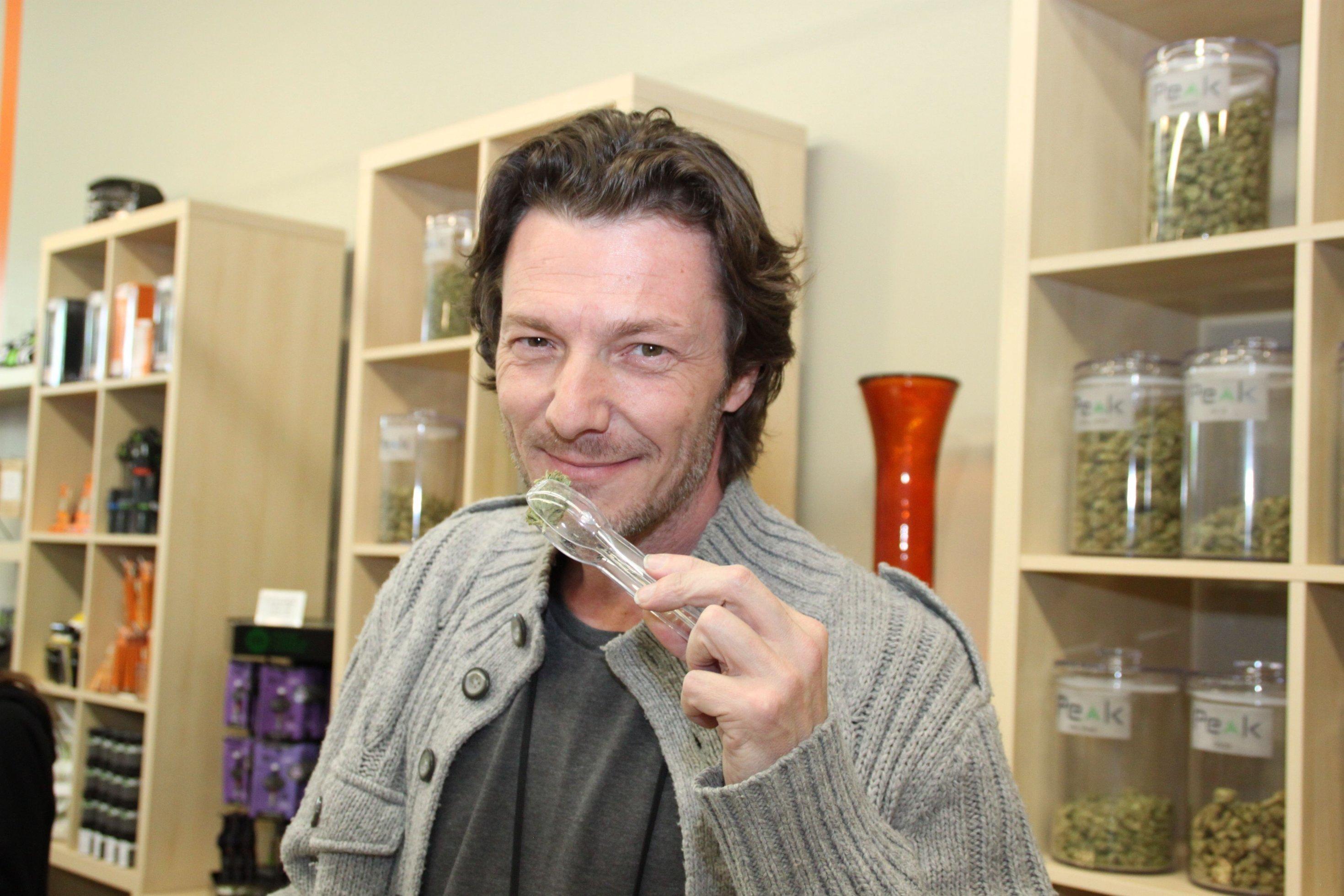 Ein Mann mittleren Alters hält Marihuana-Blüten in einer Zange.