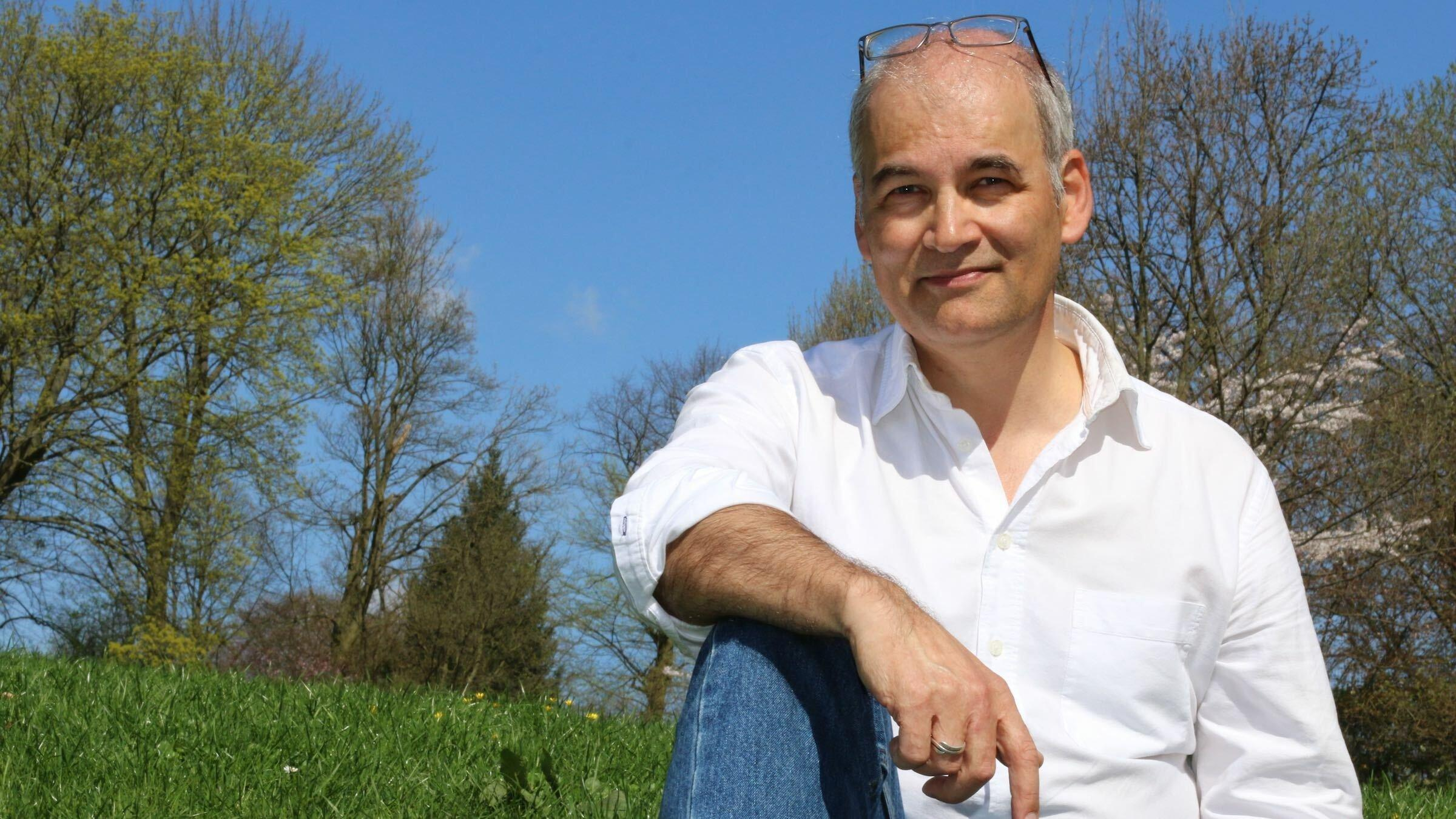 Der Journalist Christopher Schrader sitzt im weißen Hemd und Jeans auf einer Blumenwiese in einem Park am Elbhang. Er hat die Brille auf die Stirn geschoben, der rechte Arm liegt auf dem aufgestellten Knie.