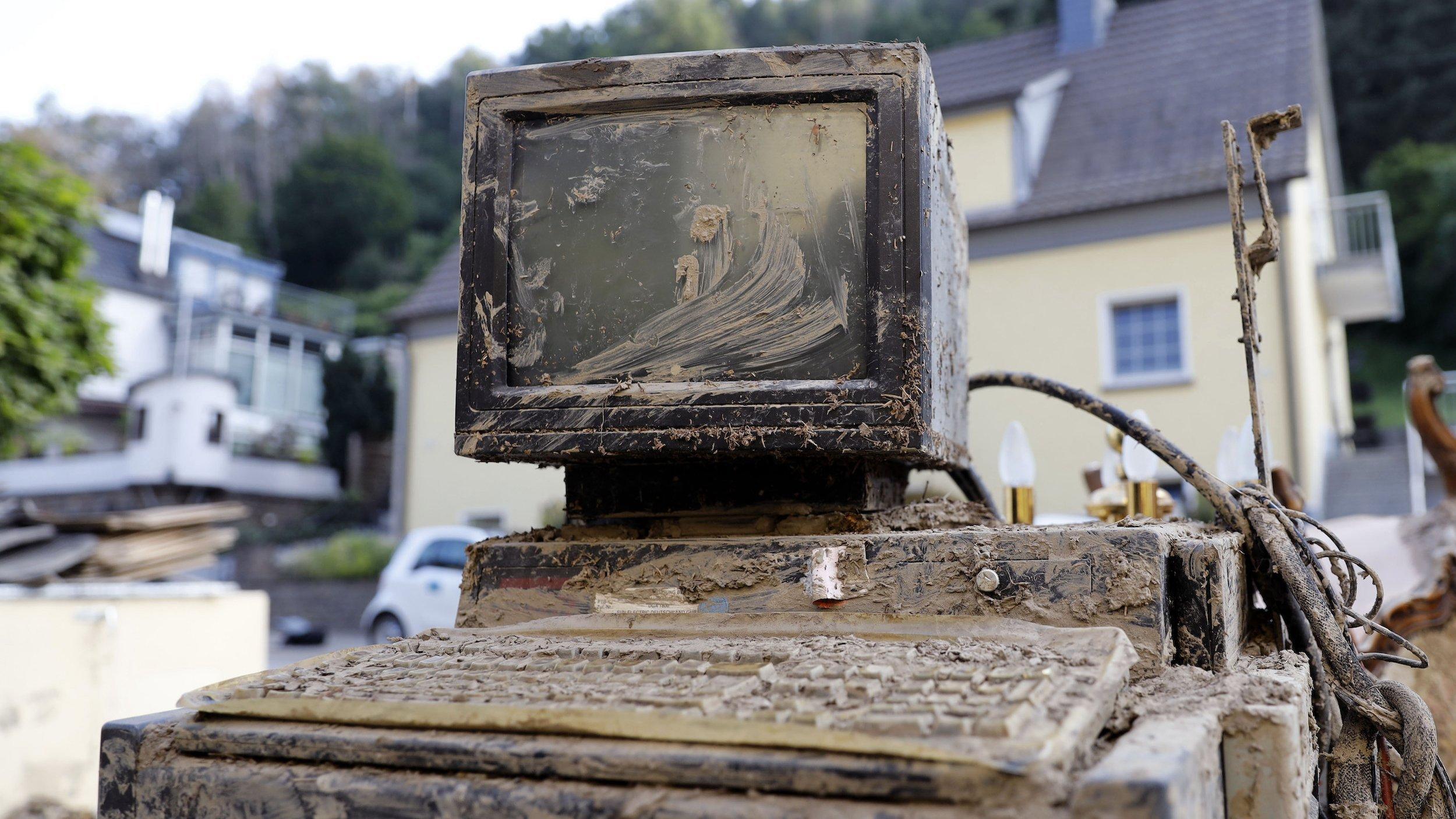 Im Bild ist ein verschlammter Computerbildschirm samt Desktop und Tastatur aus dem Flutmüll in der Ortschaft Altenahr zu sehen. In der Ortschaft zerstörte die Flut im Juli 2021viele Häuser.
