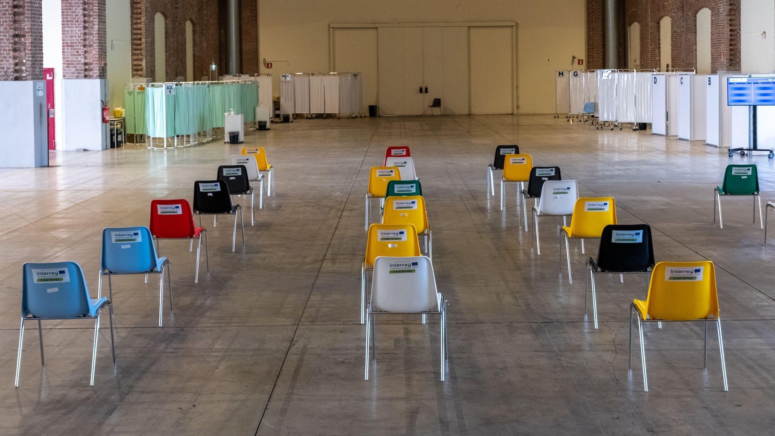 Das Bild zeigt den Wartebereich eines Corona-Impfzentrums. Alle Stühle  sind leer.