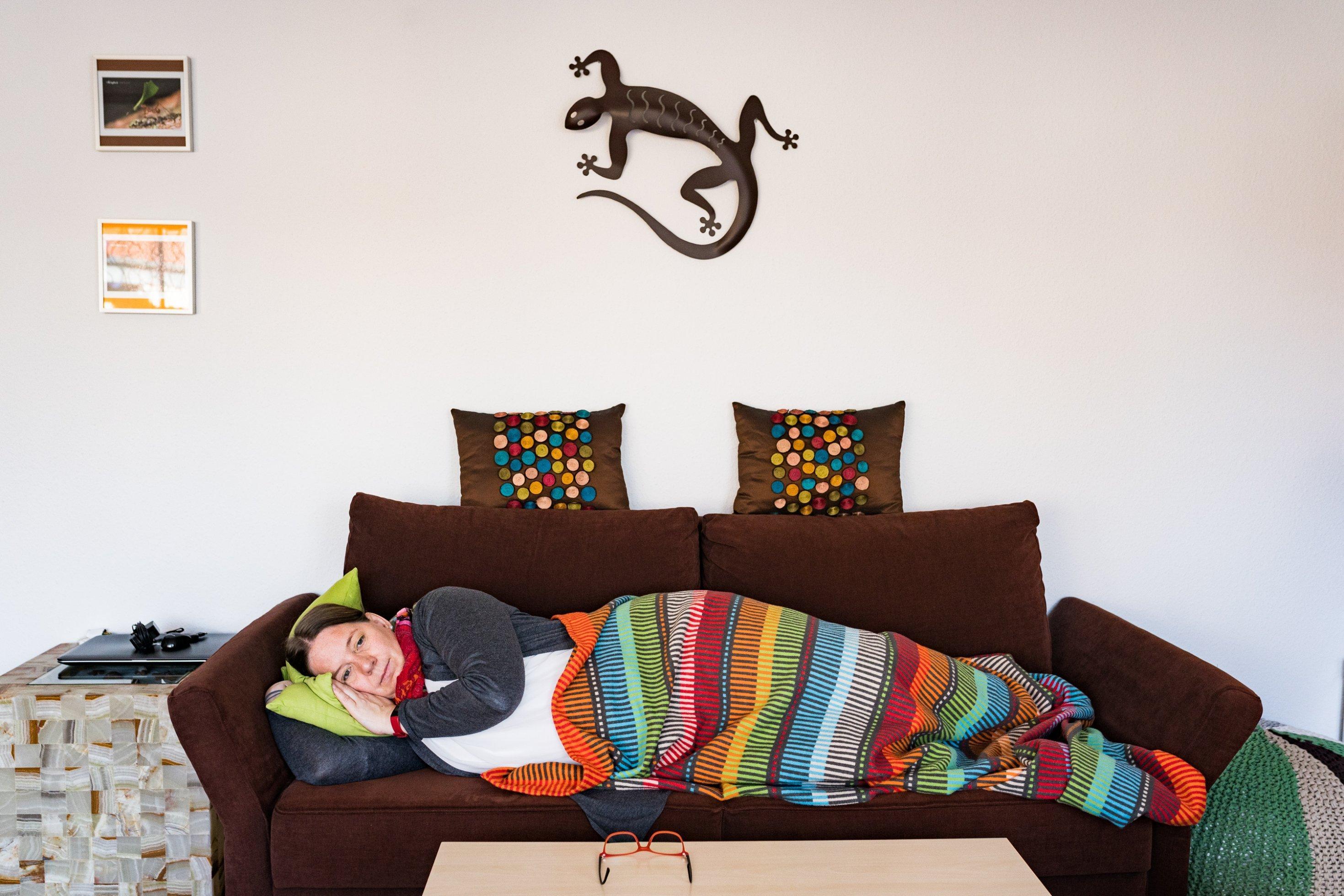 Eine junge Frau liegt in eine bunte Decke gehüllt auf ihrem Sofa und schaut erschöpft an der Kamera vorbei.