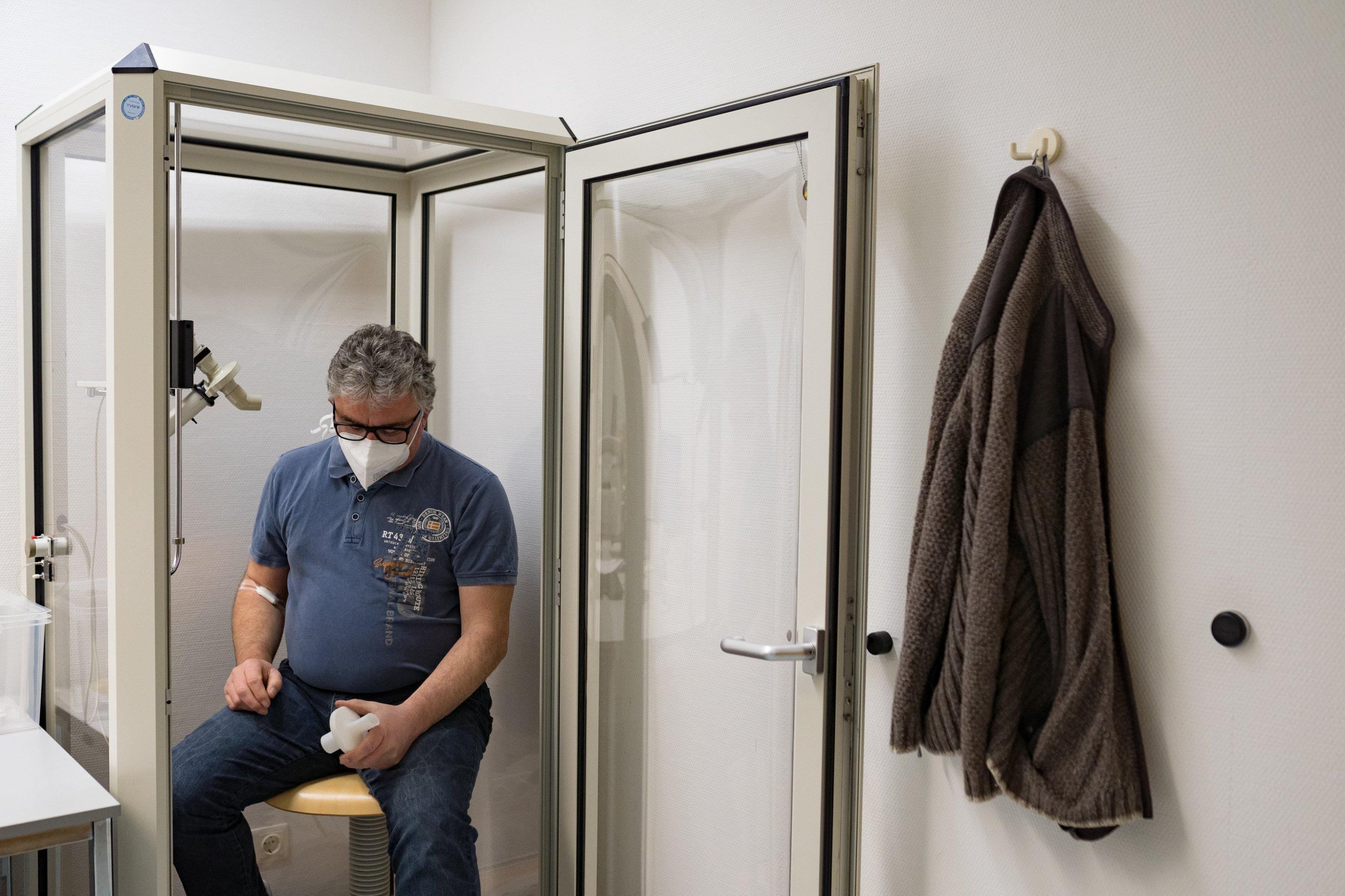 Ein älterer Mann sitzt zusammengesunken in einer Glaskabinen, in der Lungenfunktionstests gemacht werden. Er blickt auf einen Plastikaufsatz in seiner Hand, durch den er in der Kabine durchpusten muss.