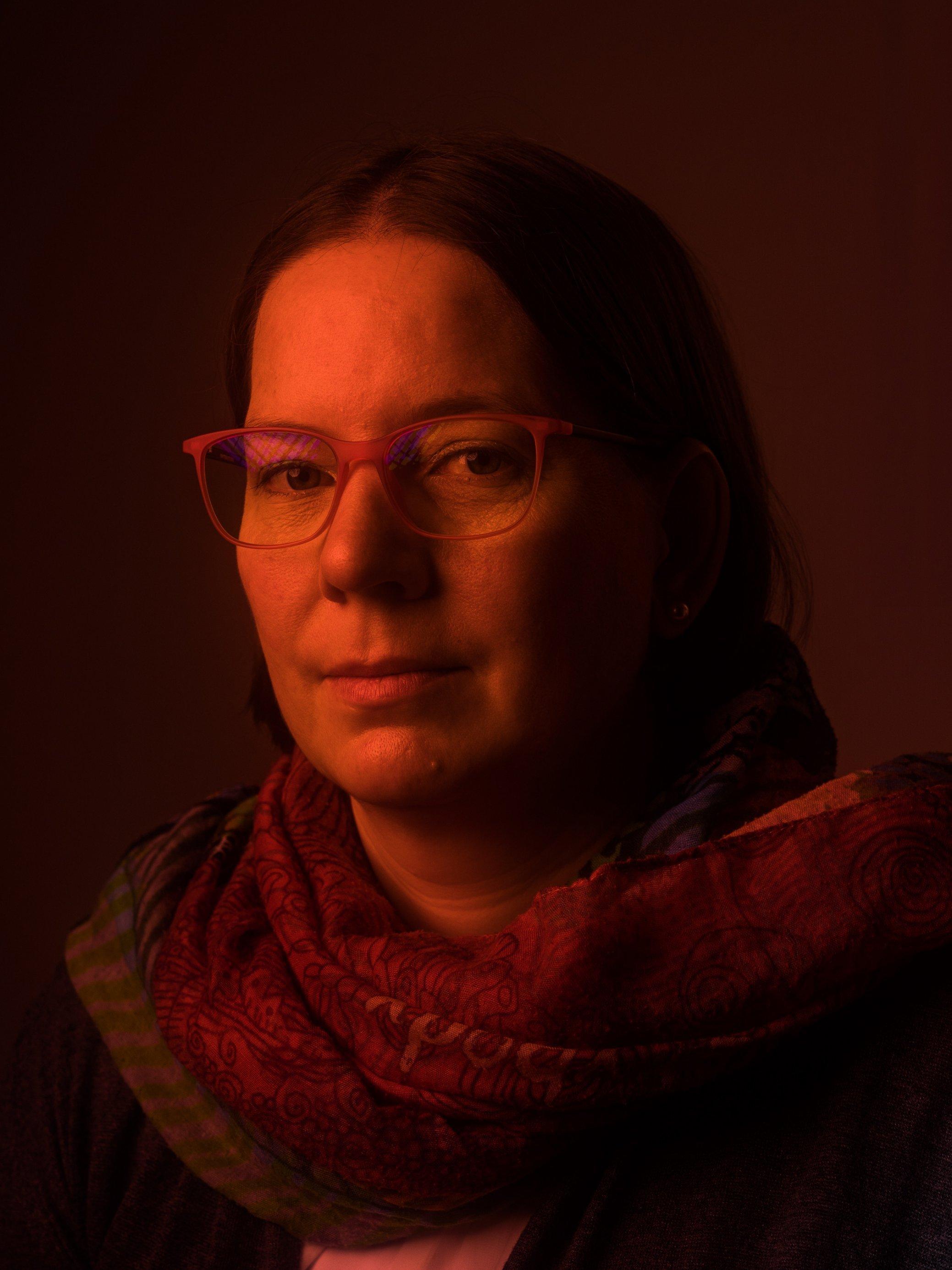 Ein mit Rotlicht verfremdetes Portrait der Long-Covid-Betroffenen Daniela Müller aus Stuttgart.