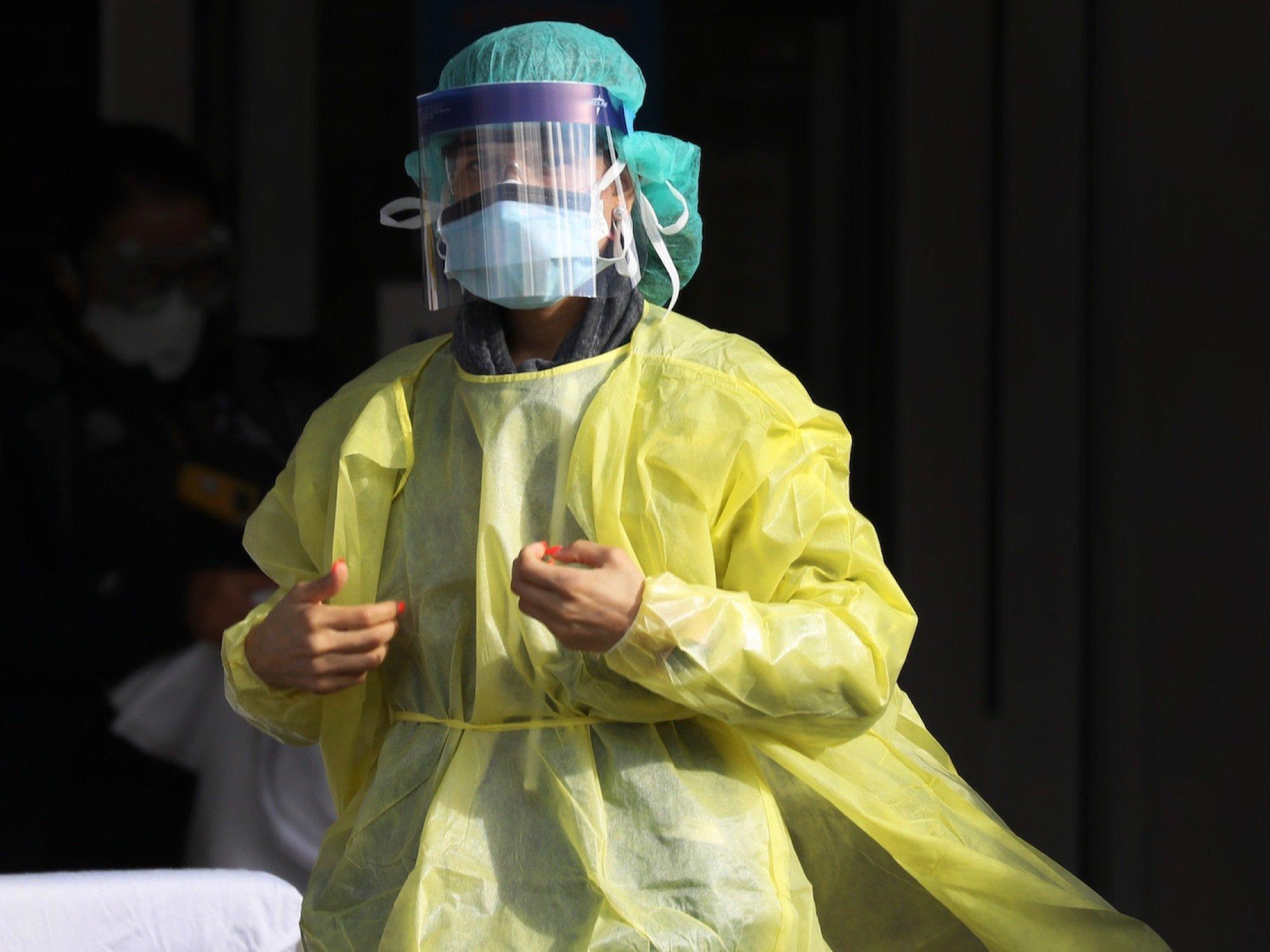 Das Bild zeigt eine Frau, die komplett in medizinische Schutzkleidung aus Plastik gehüllt ist. Man sieht ihre rot lackierten Fingernägel, aber ansonsten wenig. Sie steht vor dem Krankenhaus.