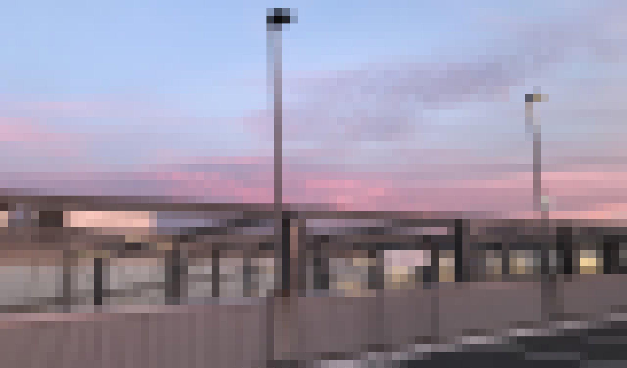 """Der Parkplatz auf dem Dach eines Einkaufszentrums in der Abenddämmerung. Auf einem Schild steht """"Ausfahrt""""."""