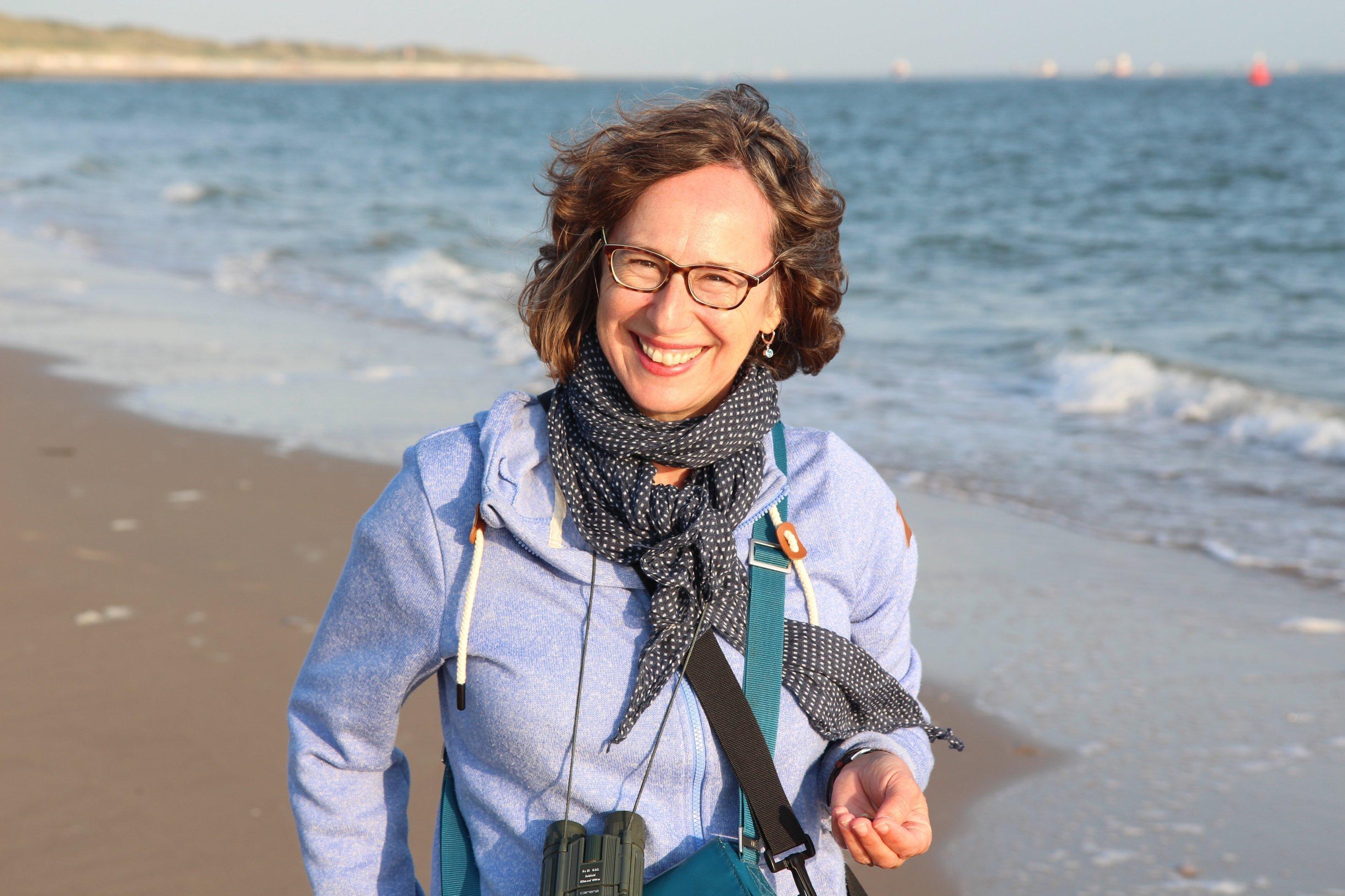 Daniela Pauli an einem Strand. Sie trägt ein Fernglas um den Hals.