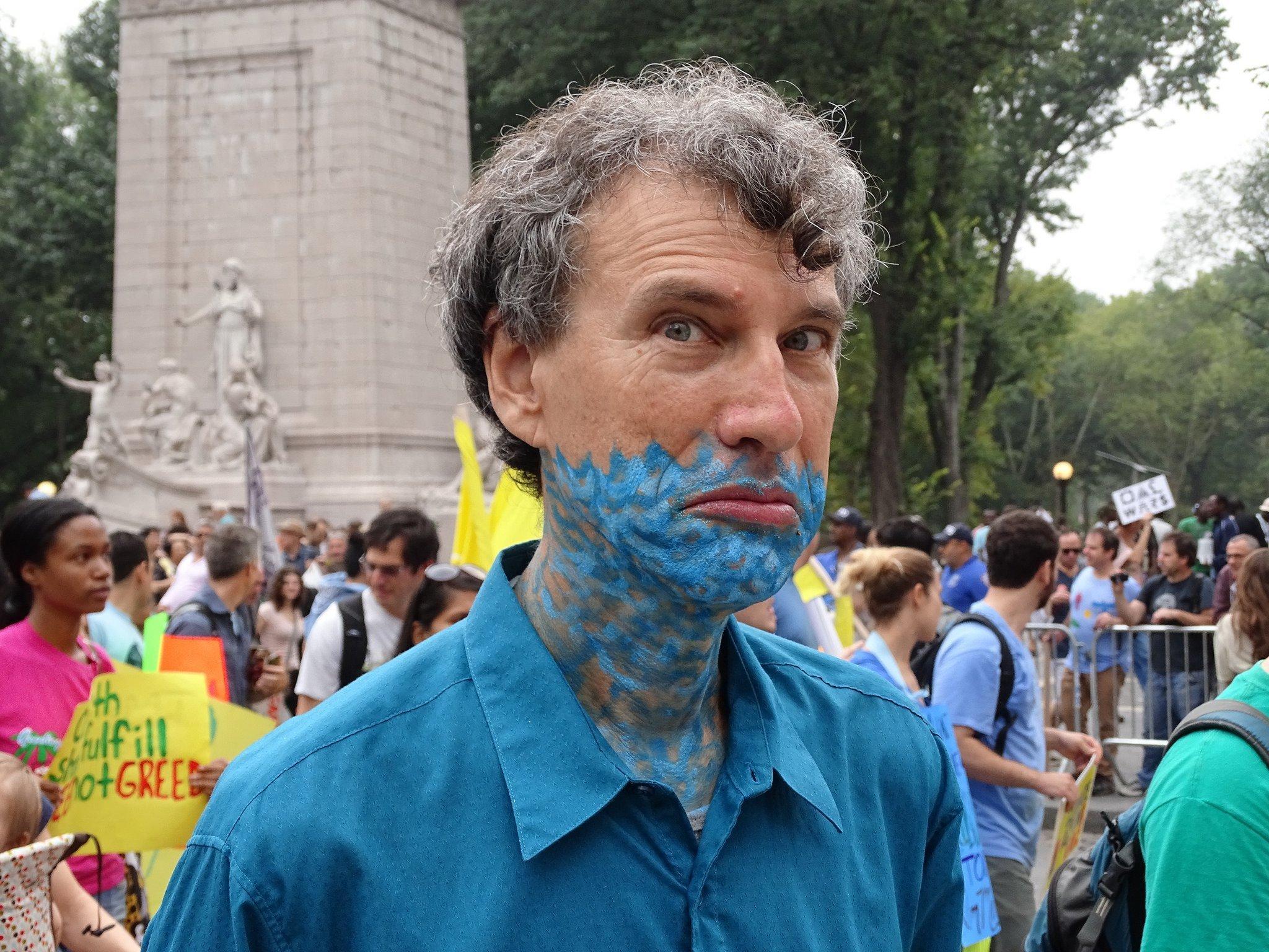Blaue Striche am Hals symbolisieren Wellen: Das Makeup sagt, das Wasser steht ihm nicht nur bis zum Hals, sondern schon bis zur Oberlippe. Der Blick unterstreicht die Botschaft. Ein Demonstrant beim Peoples Climate March 2014.
