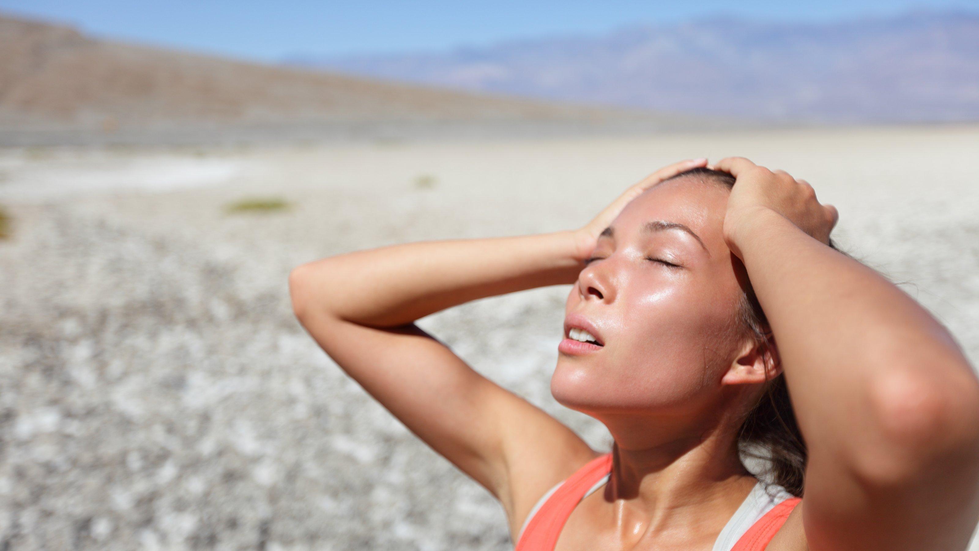 """Eine junge Frau in der Wüste """"Tal des Todes"""". Sie hat die Augen geschlossen, schwitzt, hält die Hände an den Kopf und sieht erschöpft aus. Ihr Mund ist leicht geöffnet und das Gesicht von der Sonne beschienen."""