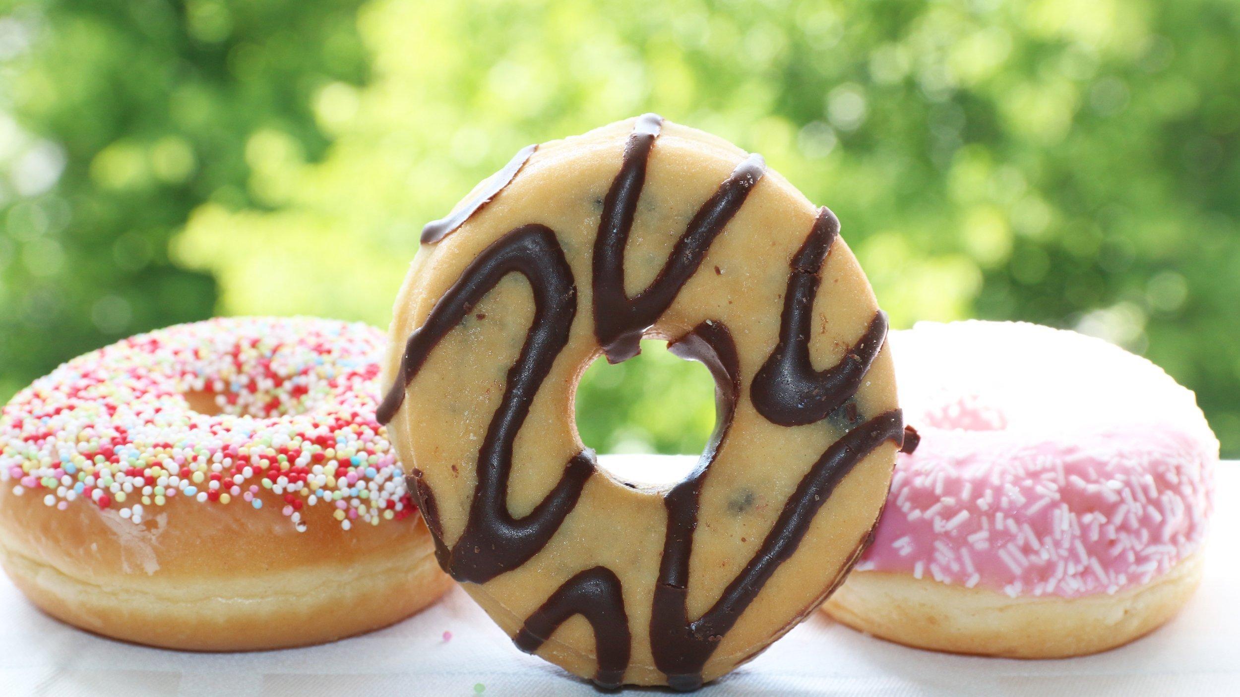 Drei Donuts liegen auf einen weißen Tuch vor einem offenen Fenster, der mittlere steht so auf der Seite, dass man durch das Loch blicken kann. Der linke ist mit Zuckerperlen verziert, der mittlere mit Schleifen von Schokoguss, der rechte mit rosa Zuckerguss. – Hefeteig, Loch in die Mitte, frittieren und verzieren – Doughnut oder Donut heißt die Kalorienbombe.
