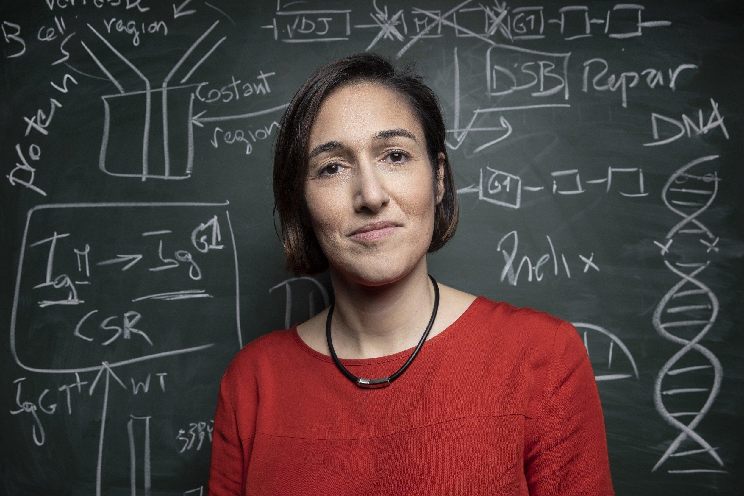 Die Immunologin und Genetikerin Michela Di Virgilio steht vor einer Tafel mit Skizzen der DNA und Zeichnungen formelartiger Strukturen, die Bestandteile des Erbguts darstellen sollen.