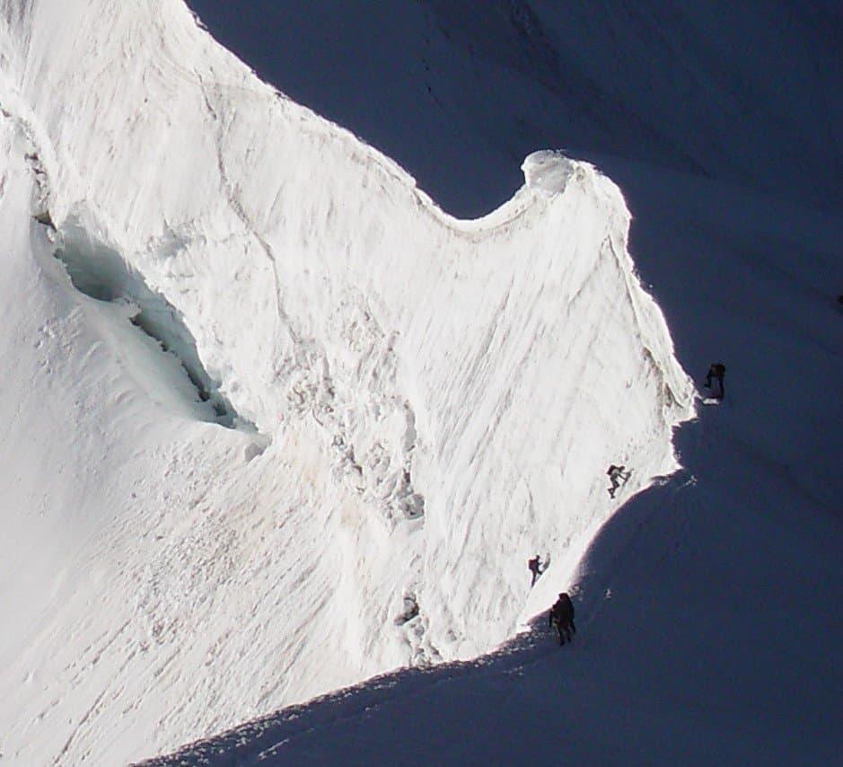 Zwei Kletterer hängen noch in der Steilwand, andere begehen weiter oben einen Firngrat.