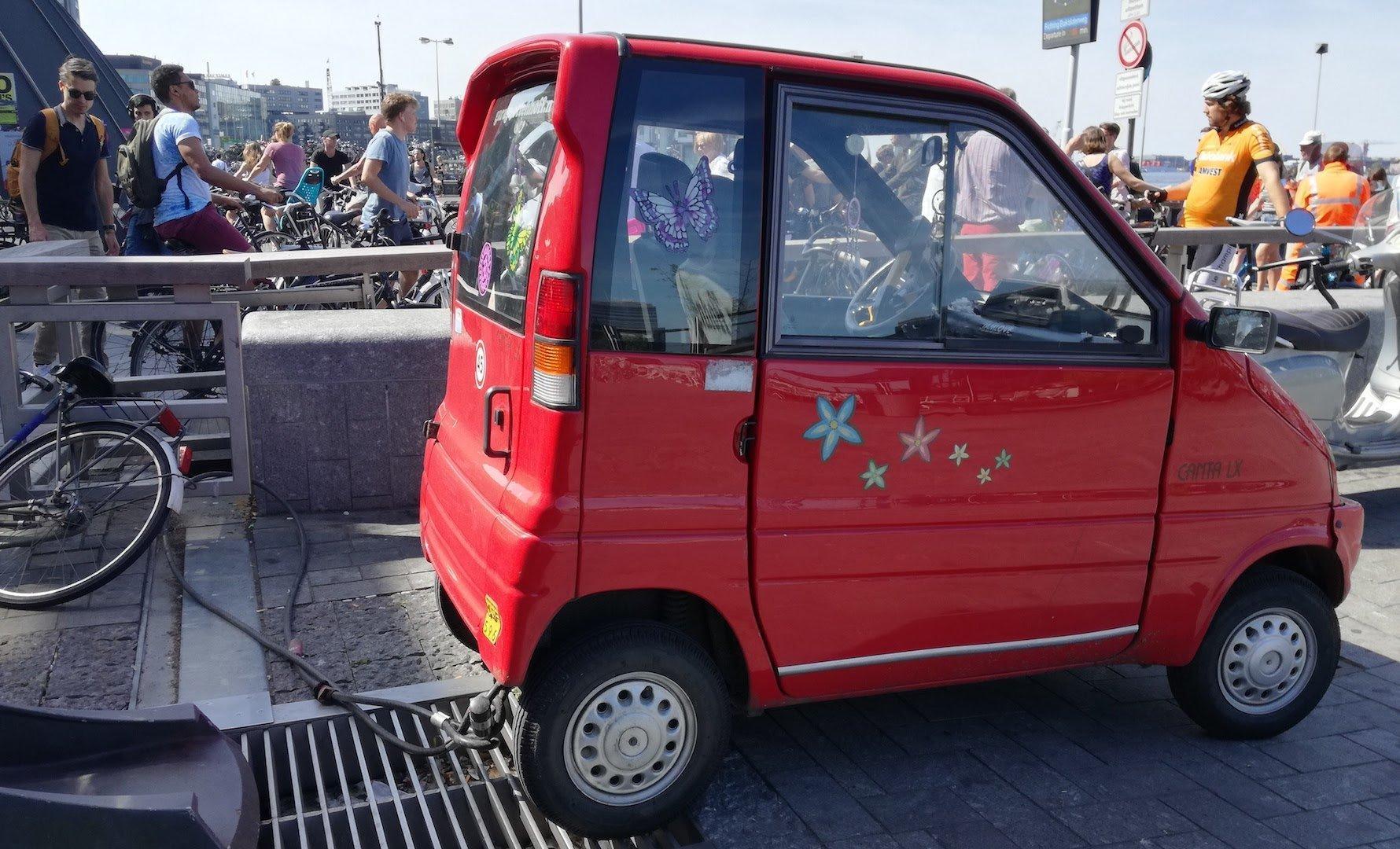 Ein kleines rotes E-Auto steht an einer Ladestation. Im Hintergrund sind Menschen zu sehen.