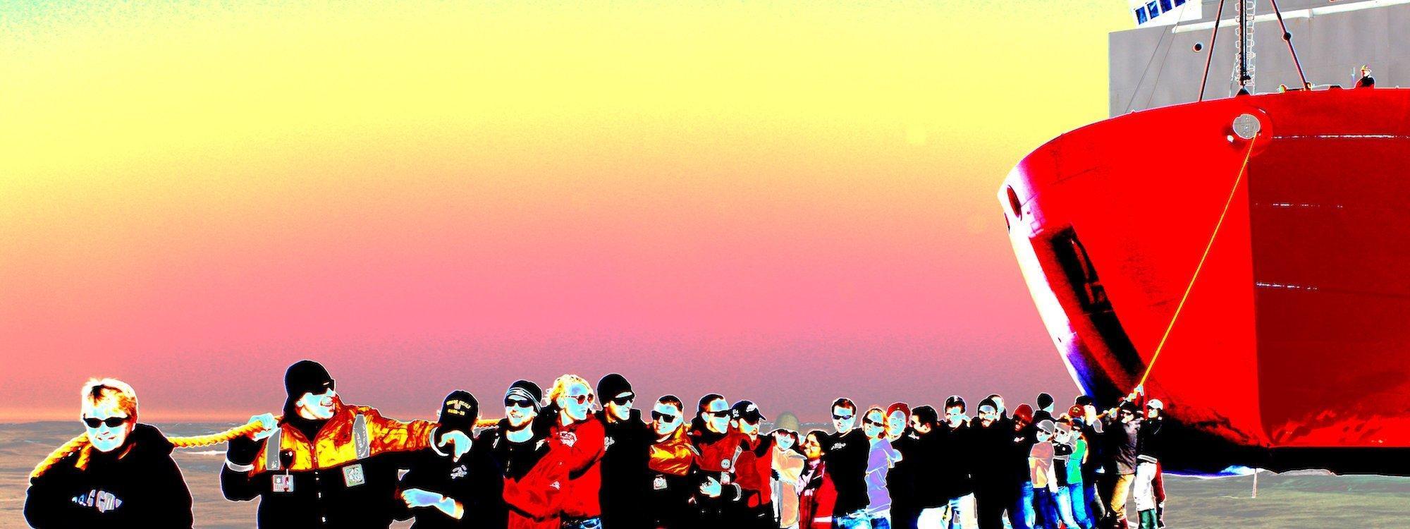 """Eine Reihe von Menschen, angeführt von der Kapitänin, steht auf dem Eis und zieht an einer Trosse, die zum Bug eines Eisbrechers mit rotem Rumpf führt. Bei der Icescape-Mission der Nasa posiert die Besatzung des US-Coast-Guard-Schiffs """"Healy"""" 2011."""