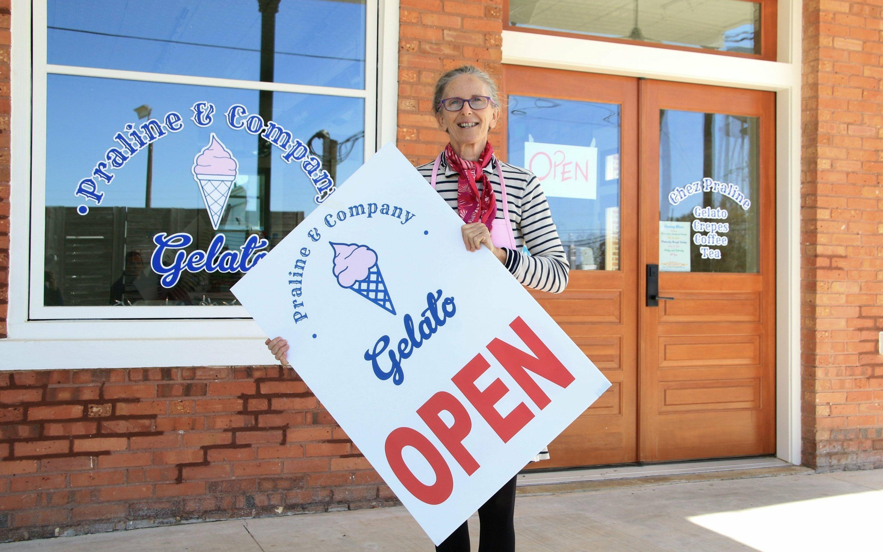 """Eine ältere Dame hält ein Schild in die Höhe. Darauf steht """"Open""""."""
