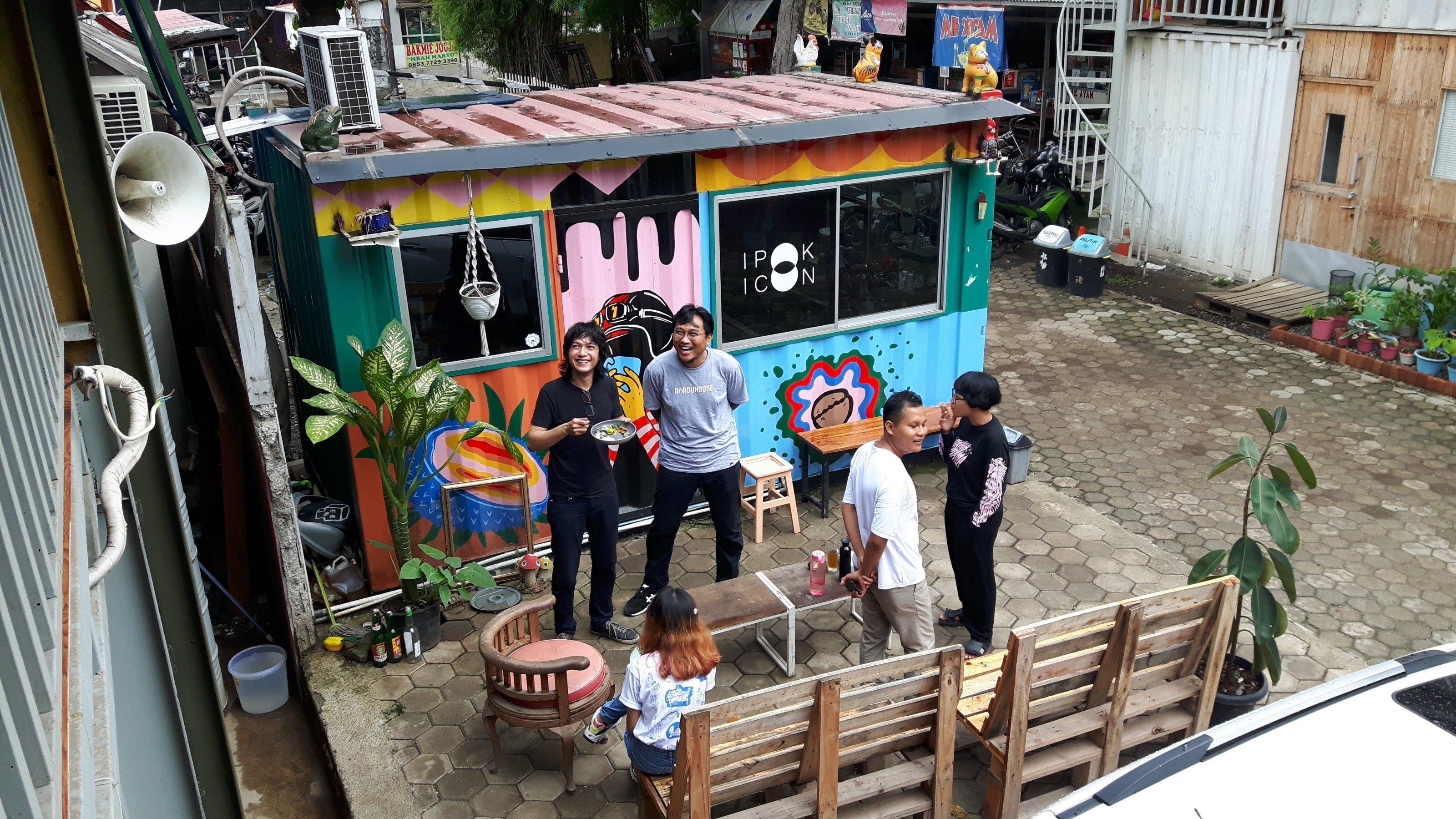 """Fünf Personen stehen und sitzen vor dem bunten Pförtnerhaus des Gudskul """"Studienkollektiv und Ekosystem für zeitgenössische Kunst"""" von ruangrupa in Jakarta"""