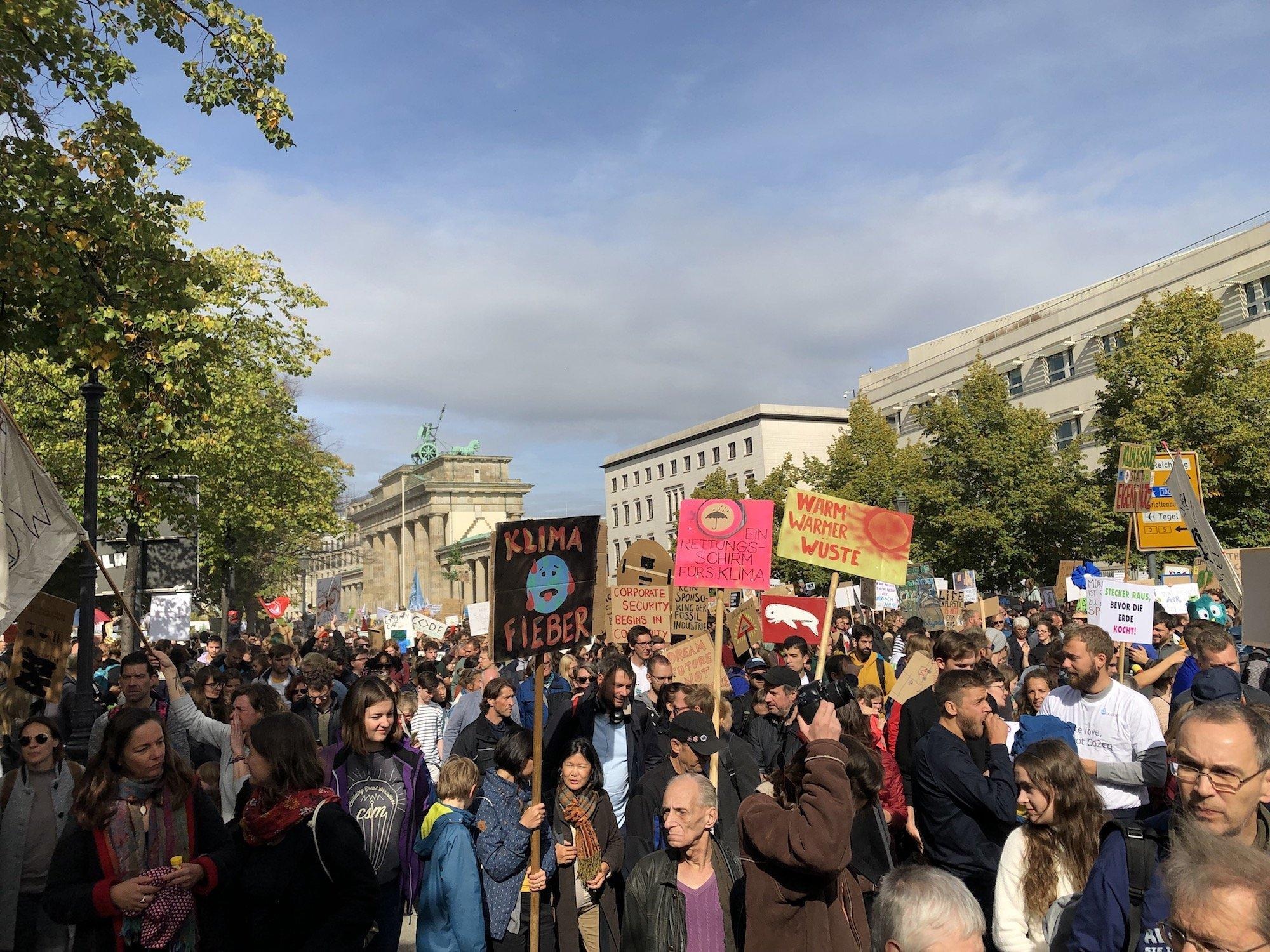 """Demonstranten der Bewegung """"Fridays for Future"""" ziehen am Brandenburger Tor vorbei. Sie halten Plakate hoch, auf denen unter anderem """"Klima Fieber"""" steht"""