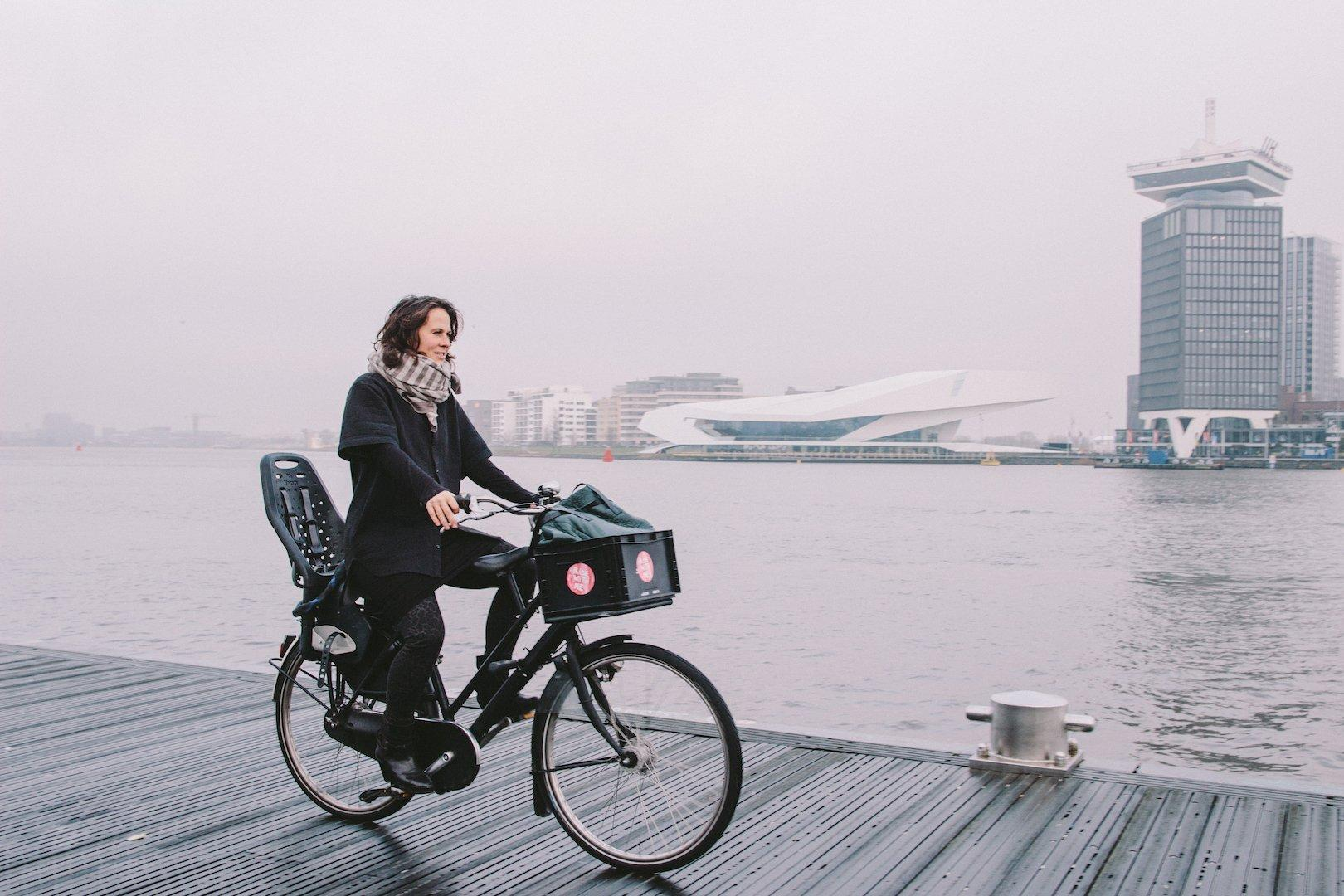Eine Frau fährt mit Fahrrad auf einem Steg am Wasser. Im Hintergrund sind Hochhäuser zu erkennen.