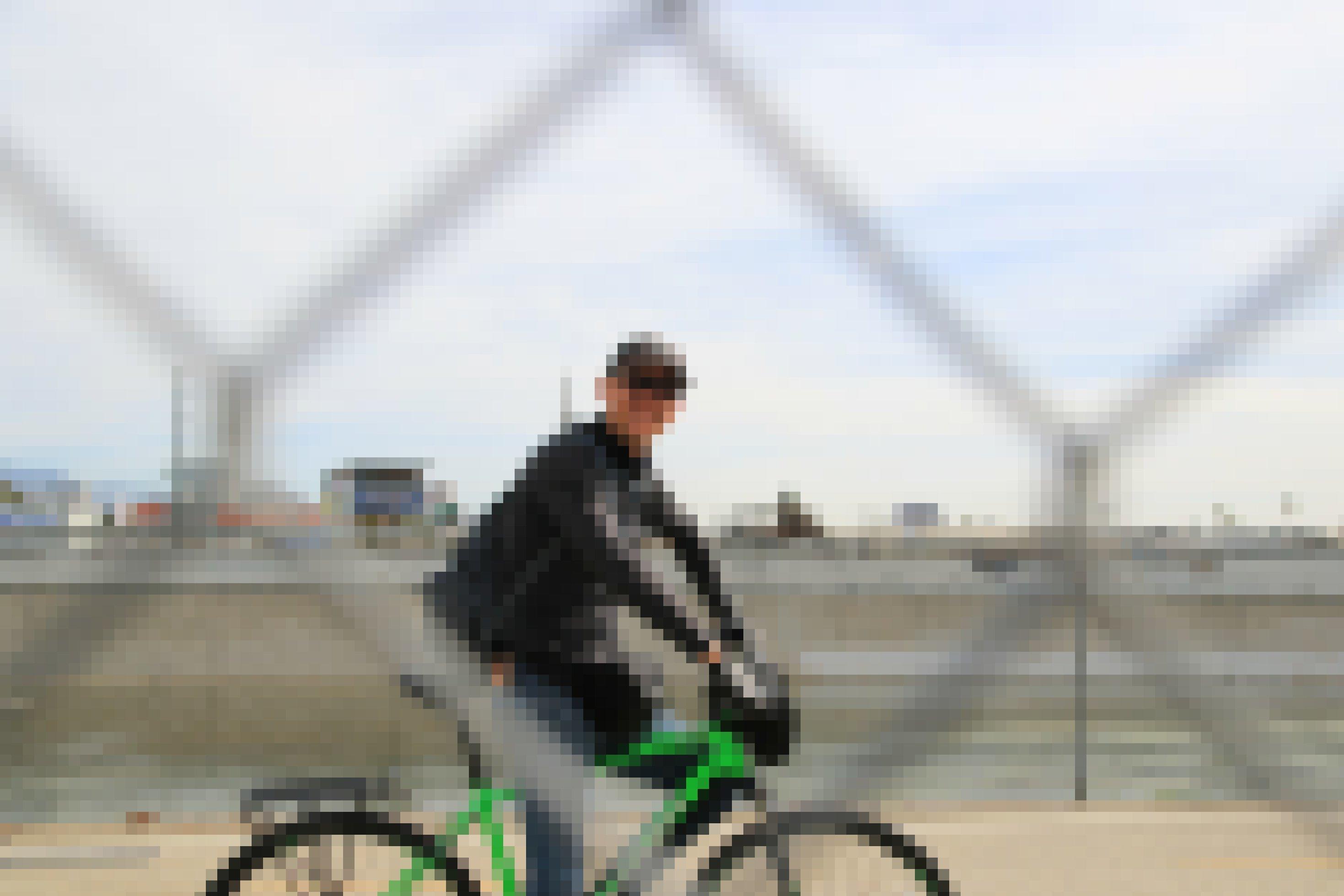 Ein Radfahrer radelt hinter einem Zaun am Fluss entlang.