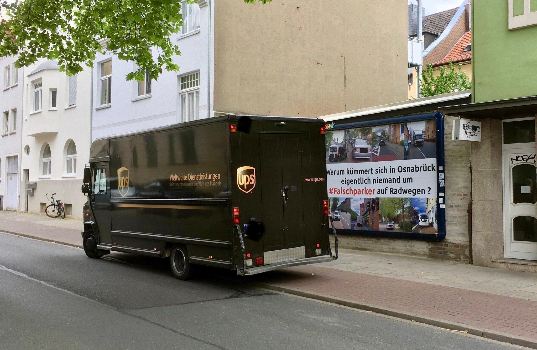 Ein großer Transporter steht mitten auf dem Rad- und Fußweg vor dem Plakat.