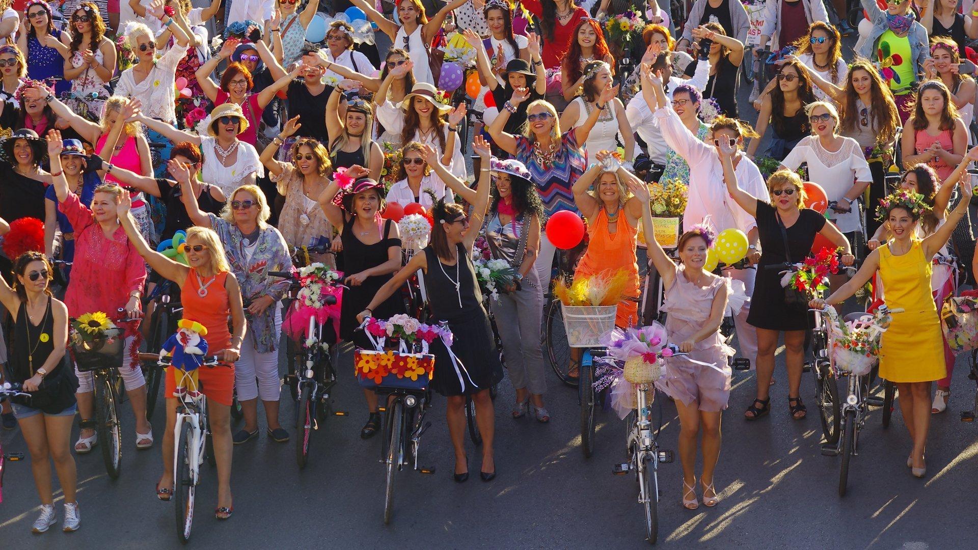Dutzende von Frauen stehen gut gelaunt mit ihren Rädern in bunten Sommerkleidern nebeneinander und winken in die Kamera. Ihre Körbe haben sie mit Blumen und Federn geschmückt.