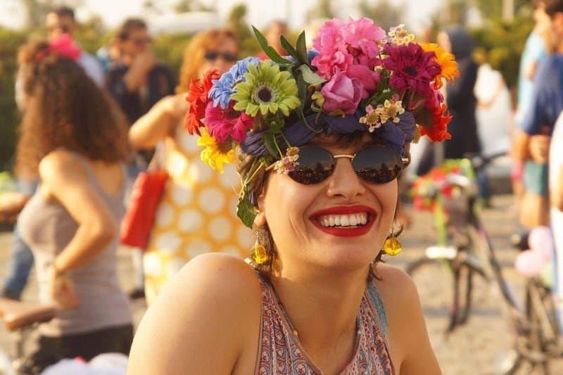 Die Portraitaufnahme zeigt eine Frau, die eine Sonnenbrille trägt und in die Kamera lacht. Sie hat sich ein Tuch um den Kopf gebunden und sich bunte Blumen ins Haar gesteckt. Im Hintergrund stehen weitere Teilnehmer der Ausfahrt.