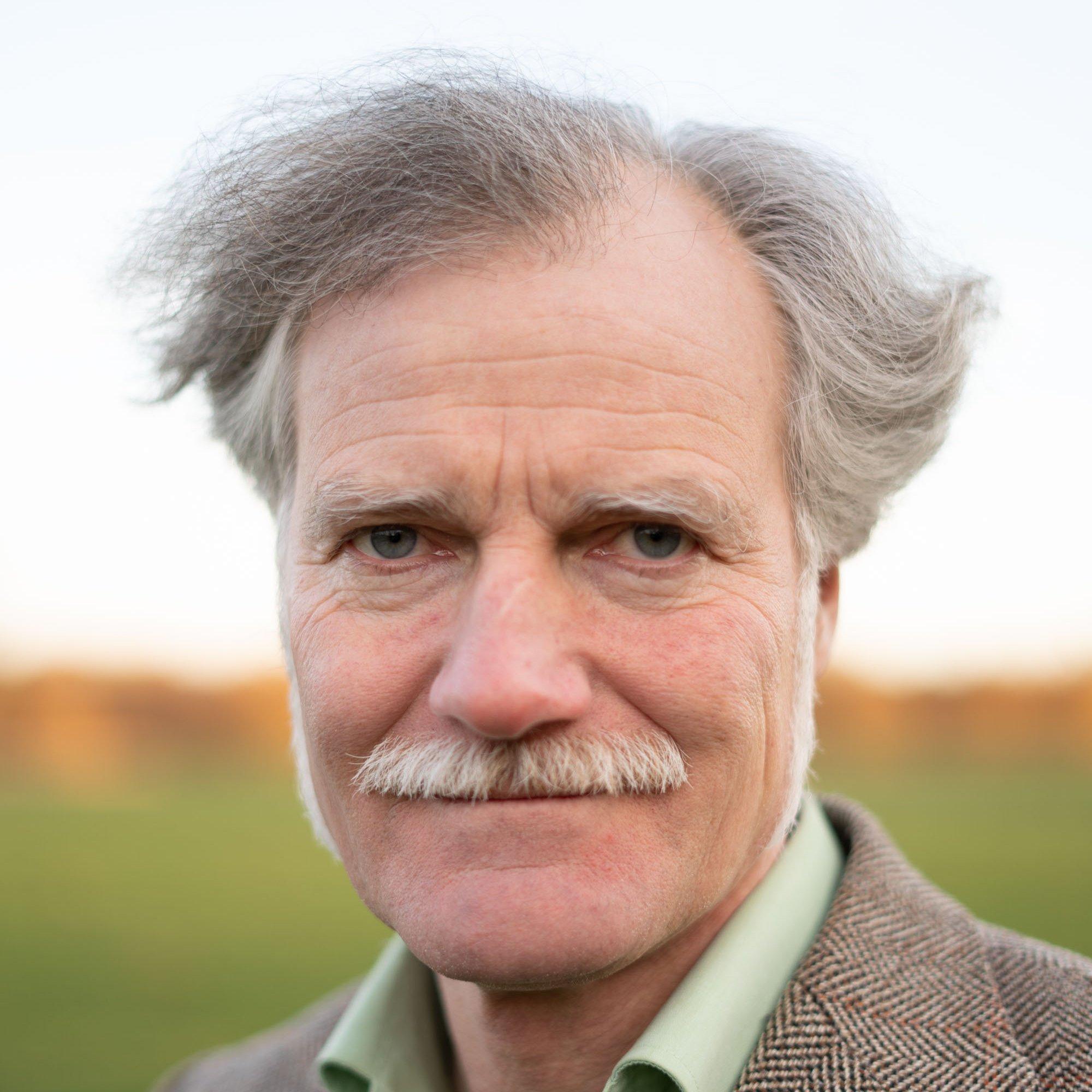 Der Field-Writer Gerhard Richter trägt eine grauen Schnurbart und die Haare als Seitenscheitel. Er trägt außerdem ein hellgrünes Hemd und darüber ein braunes Tweed-Sacko.