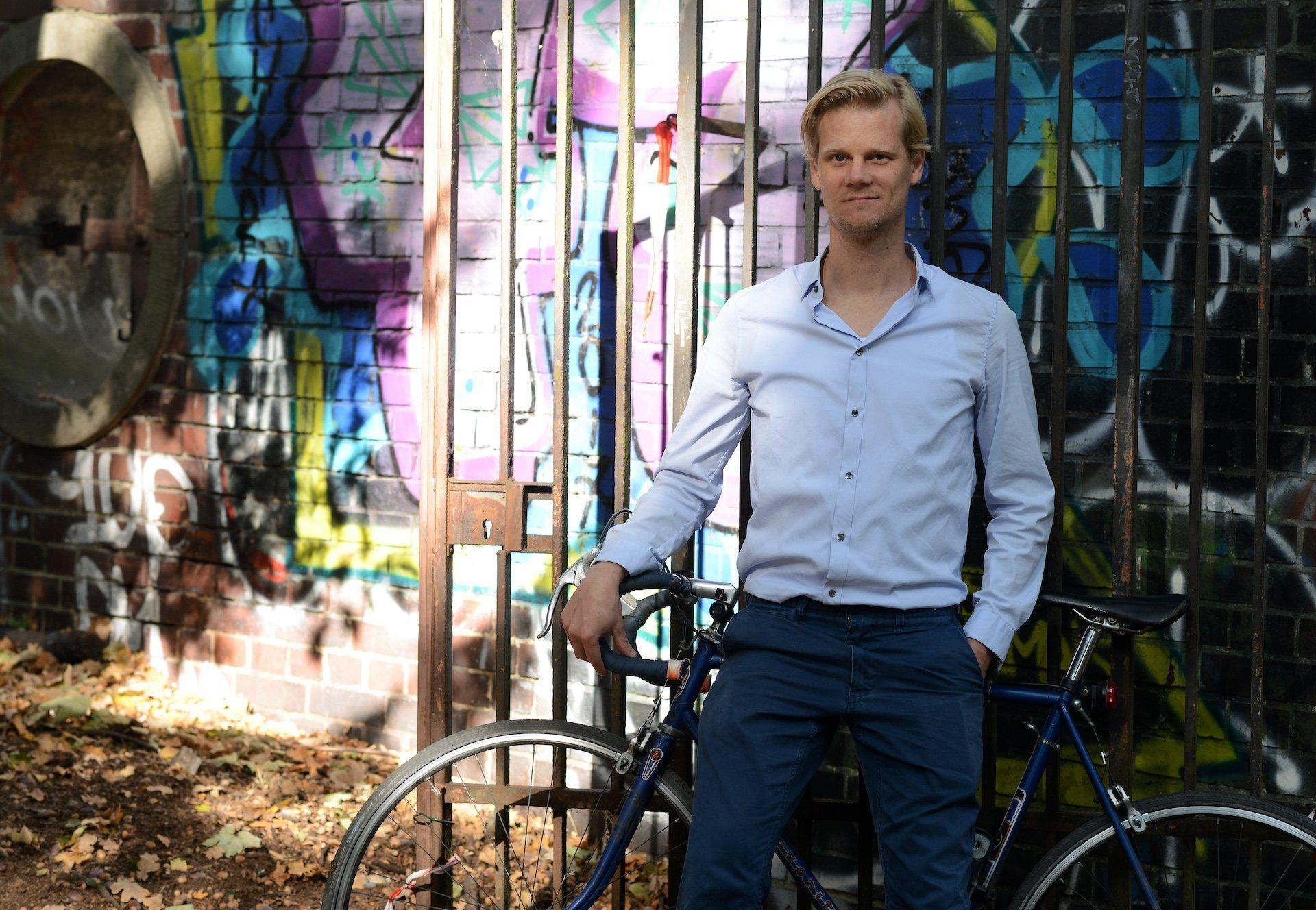 Heiko Rintelen steht vor seinem Rennrad mit dem er jeden Tag durch Berlin fährt.
