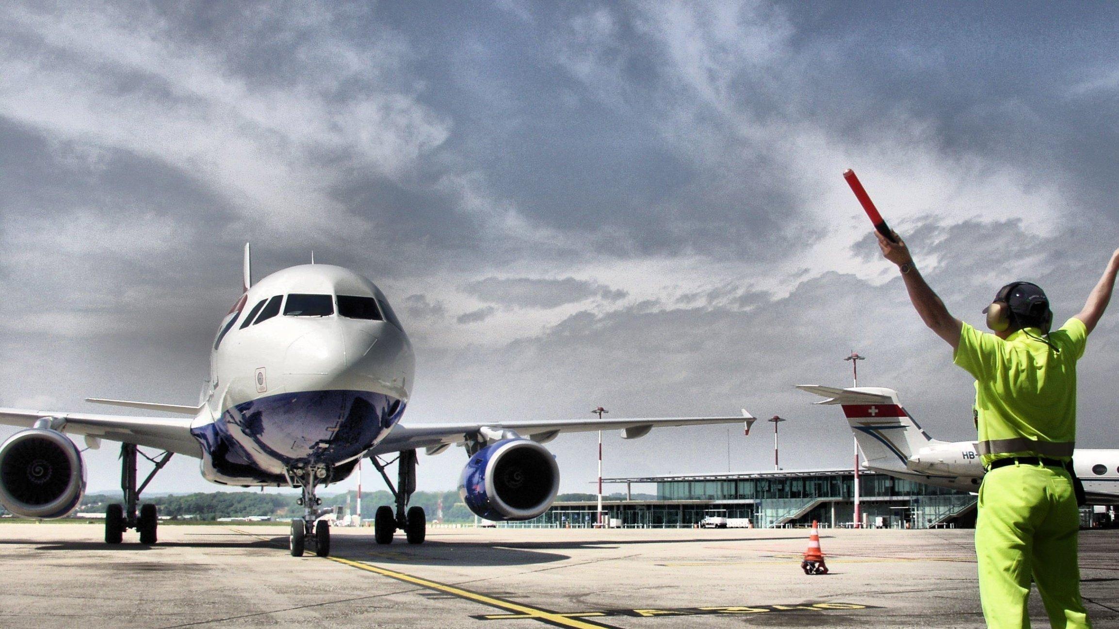 Ein Mitarbeiter des Bodenpersonals hält Signalstäbe in die Höhe, um ein Flugzeug einzuweisen.