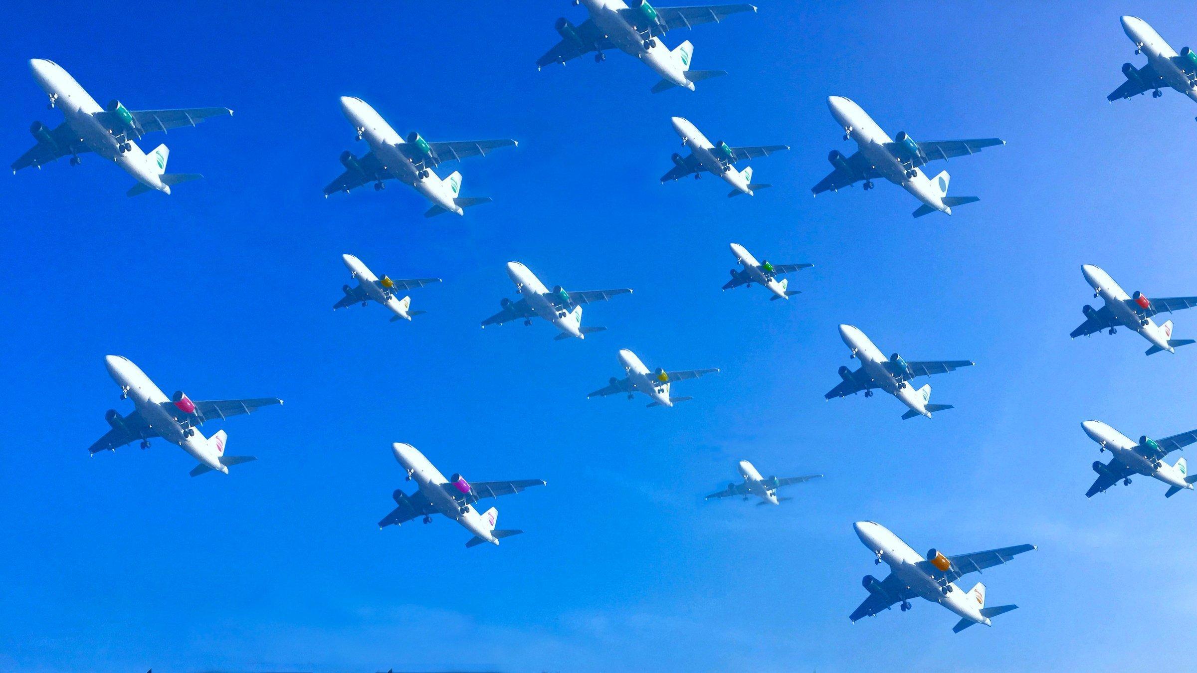An einem blauen Himmel schwebt in dieser Fotomontage mehr als ein Dutzend Flugzeuge dicht nebeneinander auf den Landeplatz zu.