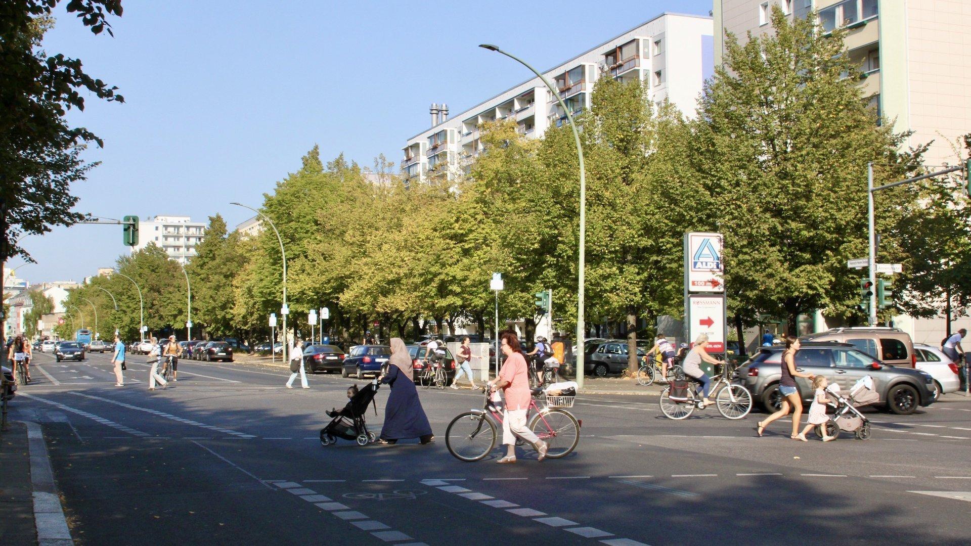 Eine breite Kreuzung in Berlin im Spätsommer. Die Sonne scheint. Zwei Frauen schieben Kinder in entgegengesetzter Richtung über die Ampel, eine weitere Frau schiebt ihr Fahrrad über die Kreuzung eine weitere fährt mit dem Rad im Hintergrund über die Kreuzung.