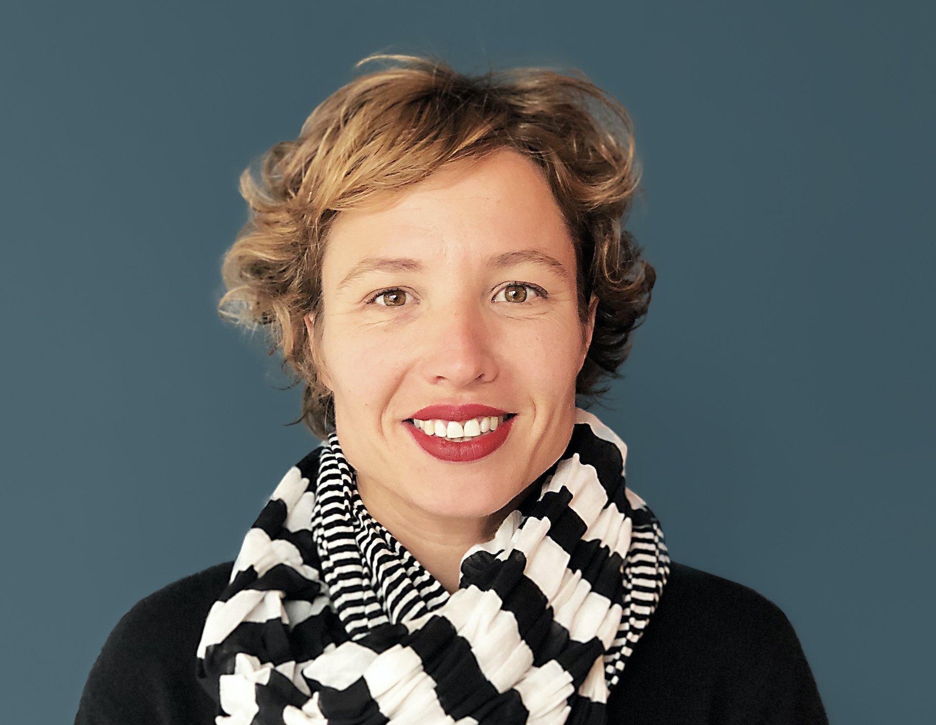 Porträtaufnahme vor dunklem Hintergrund von Lieke Ypma. Sie trägt ihre blonden, lockigen Haare kurz.