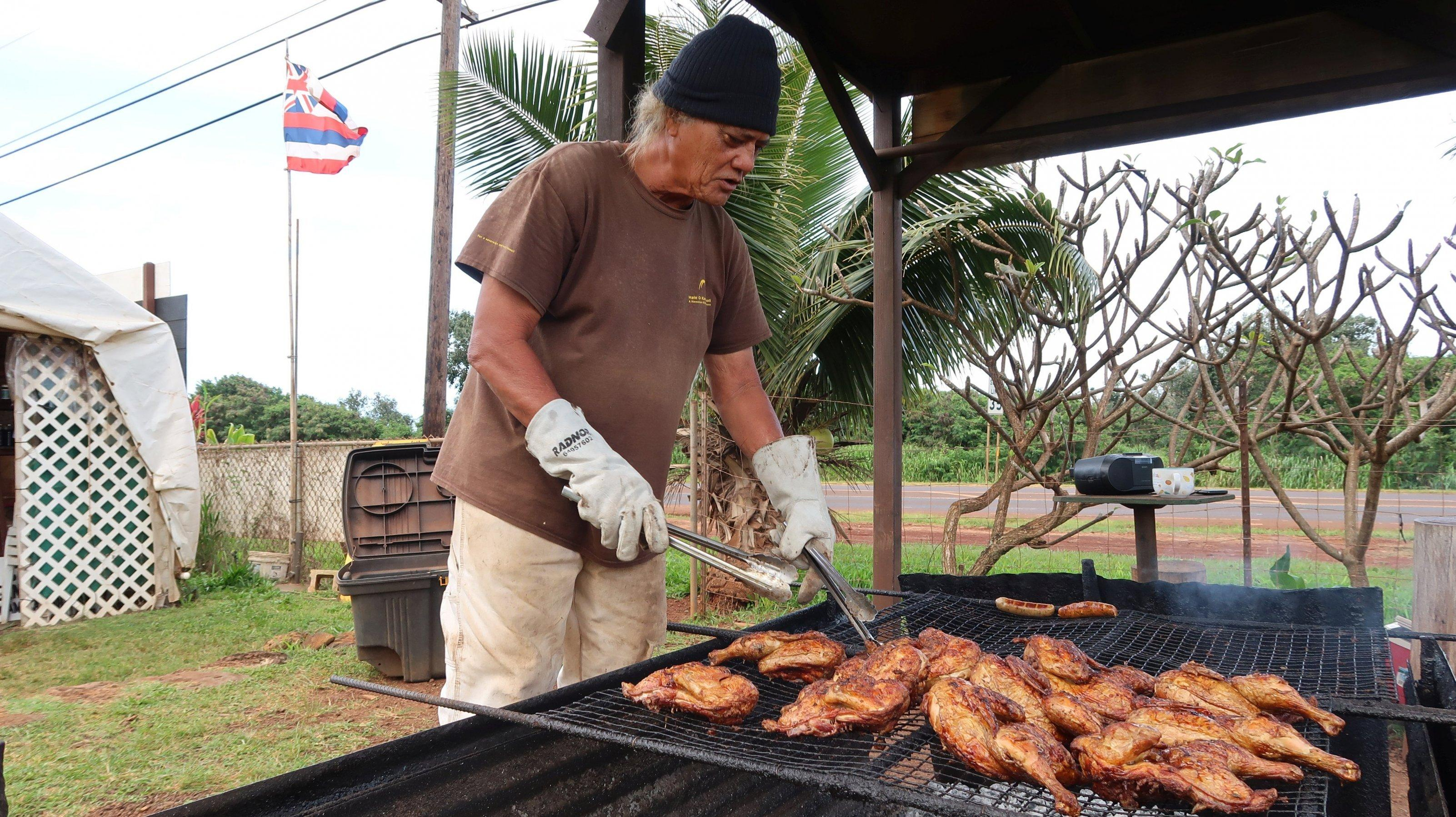 Ein älterer Herr grillt Hähnchen.