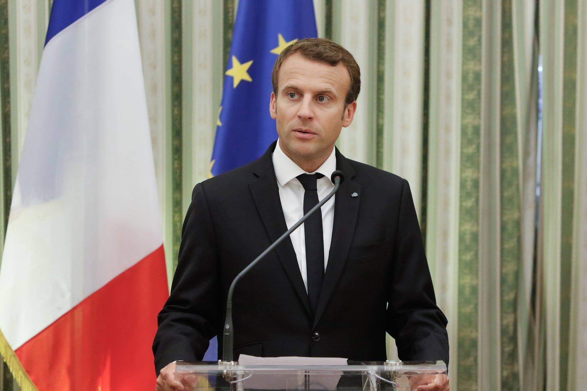 Emmanuel Macron an einem Rednerpult, die griechische und die Europaflagge im Hintergrund