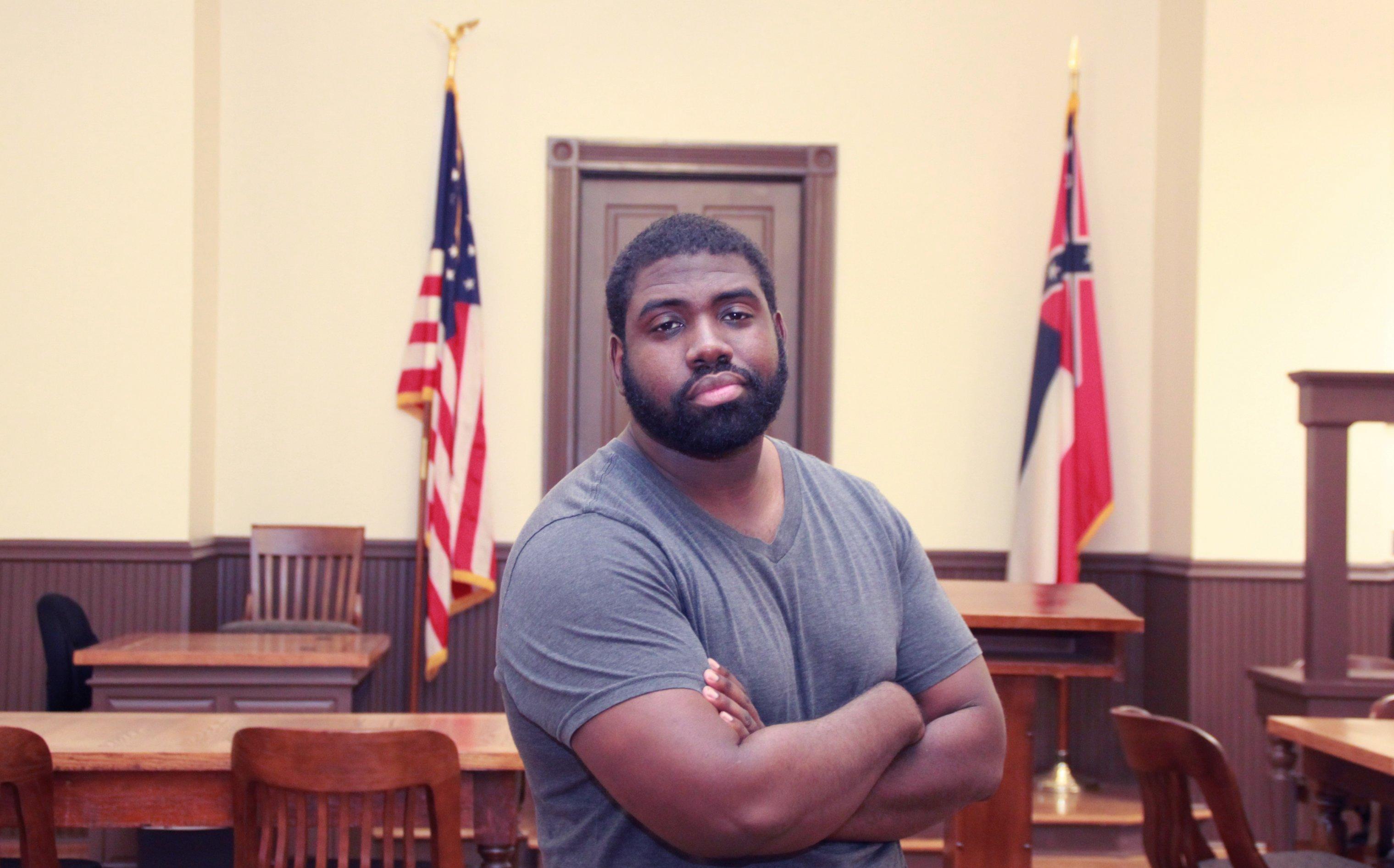 Ein dunkelhäutiger Mann steht mit verschränkten Armen in einem Gerichtssaal.