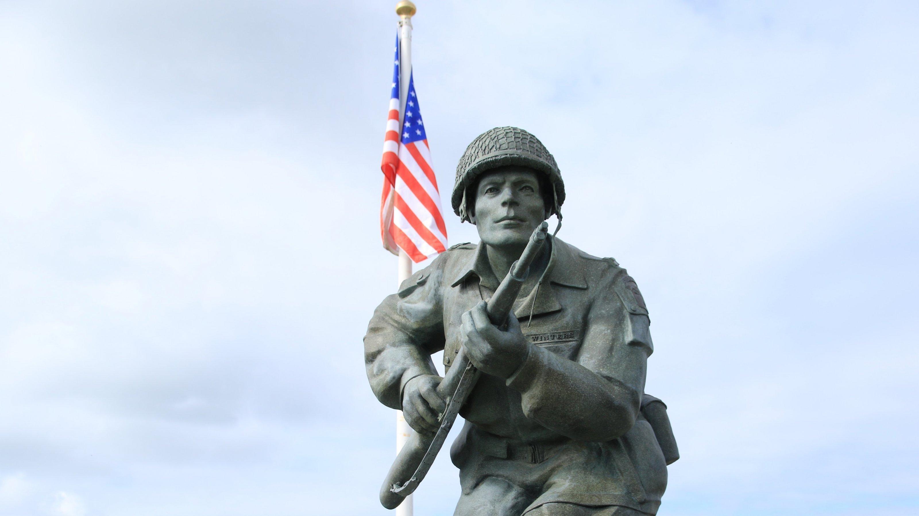 Eine Skulptur zeigt einen amerikanischen Soldaten mit Gewehr und Marschgepäck, im Hintergrund weht die US-amerikanische Fahne