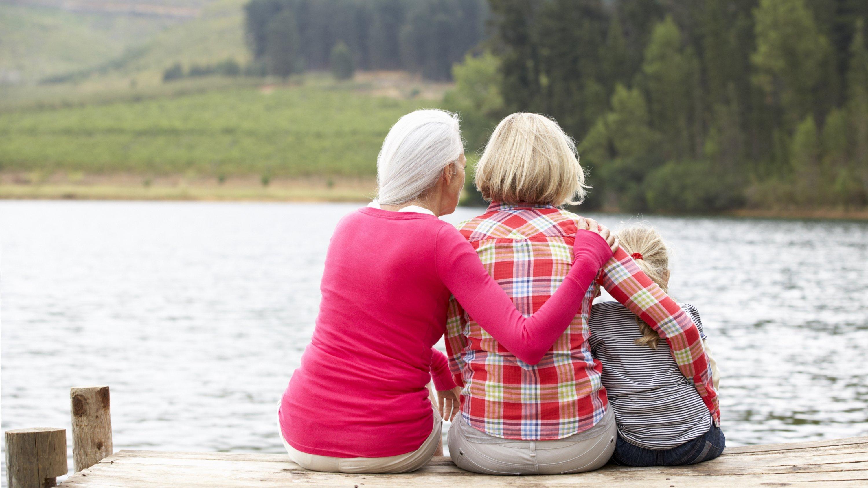 Großmutter, Mutter und Tochter sitzen auf einem Steg am See.
