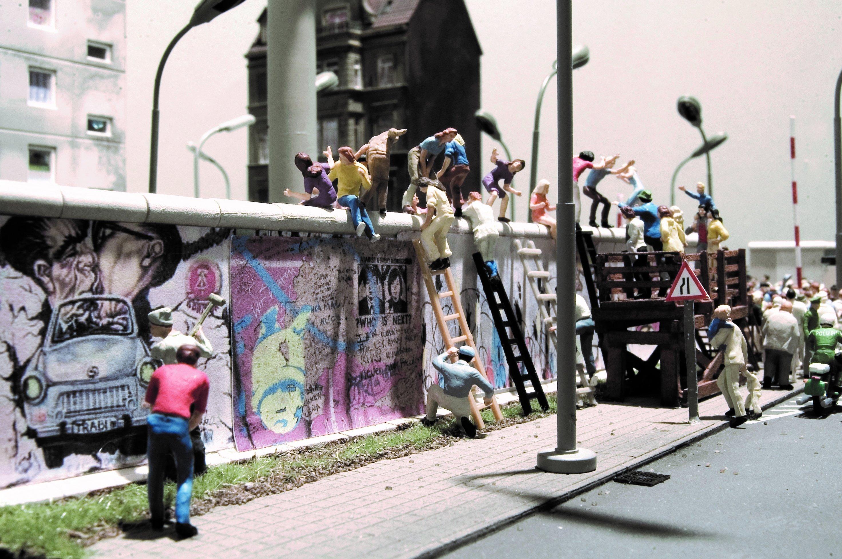 Von beiden Seiten und mit einfachen Leitern wird die Berliner Mauer am 9. November 1989erstürmt.