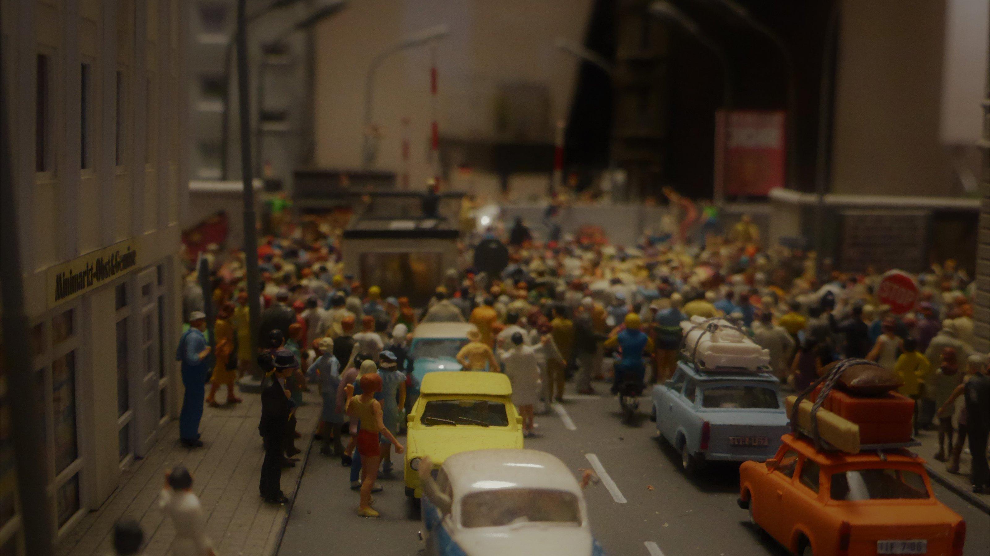 Unbepackte DDR-PKW bahnen sich einen Weg nach Westberlin, während vollgepackte Karossen bereits wieder auf dem Weg nach Hause in den Ostteil der Stadt sind.