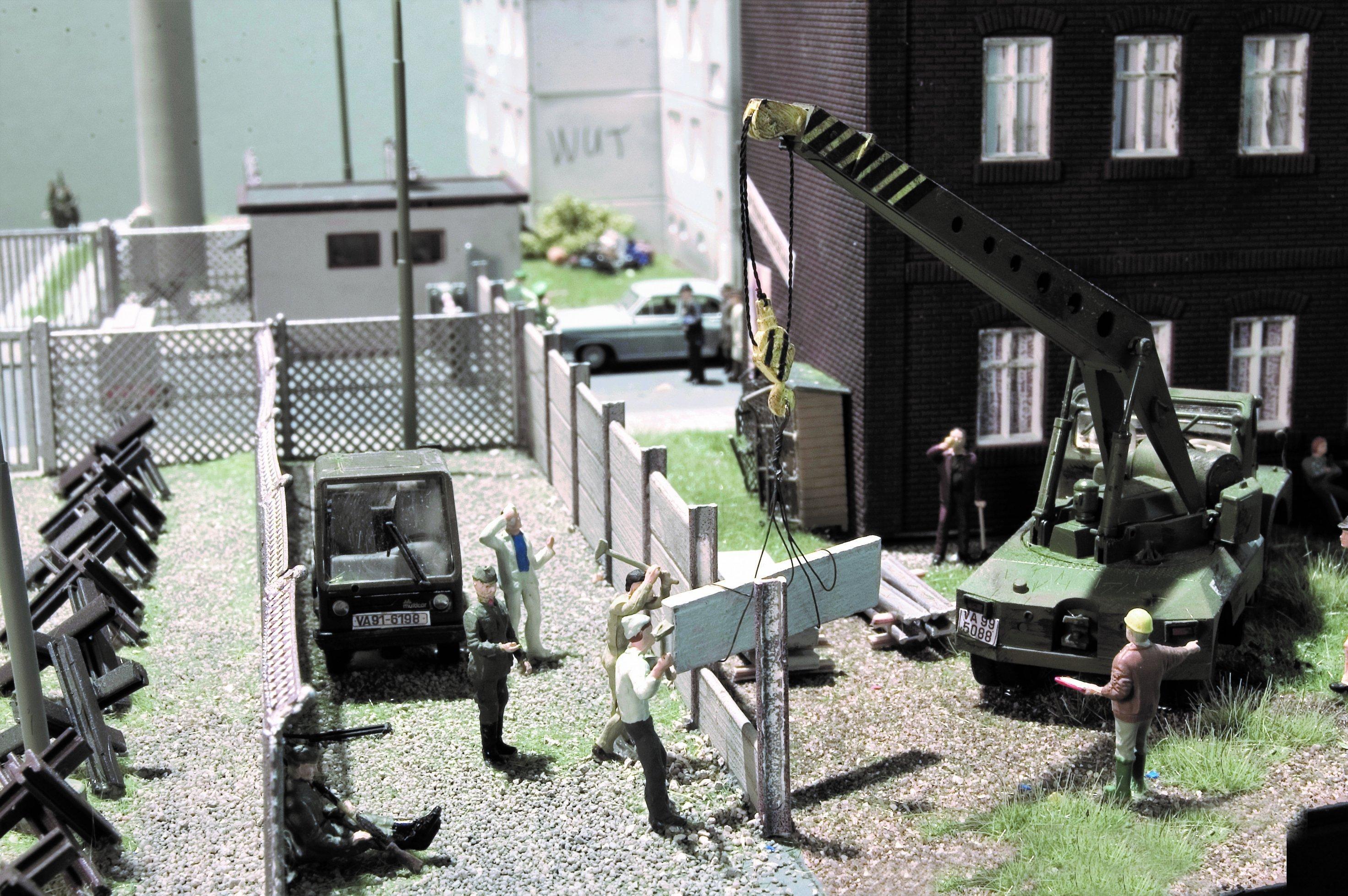 Unter militärischer Aufsicht errichten DDR-Arbeiter 1975eine modernere, sichere Mauer in Berlin.
