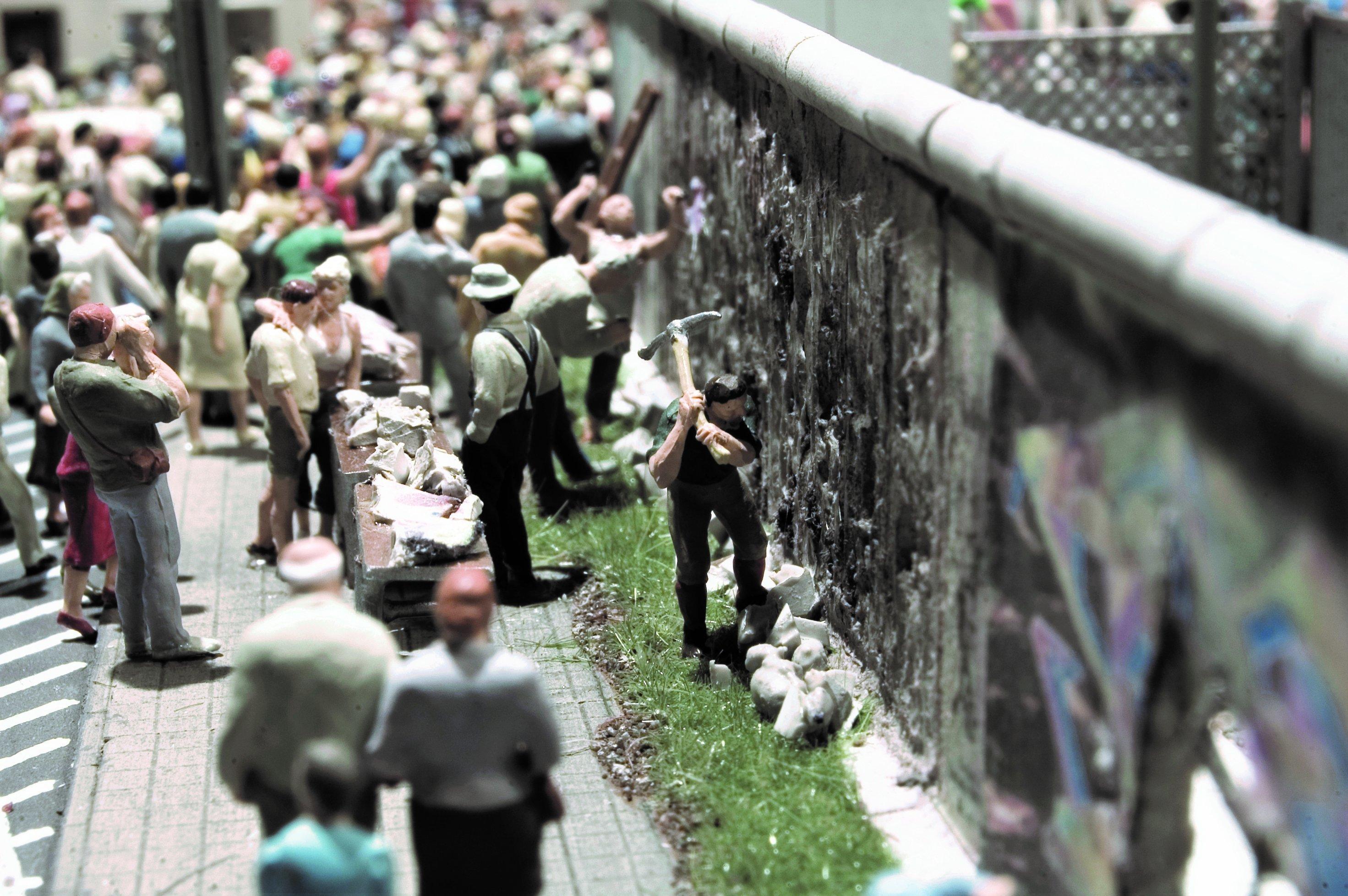 Ein Mann holt mit einer großen Spitzhacke gewaltig aus, um der Berliner Mauer ein weiteres Loch zuzufügen.