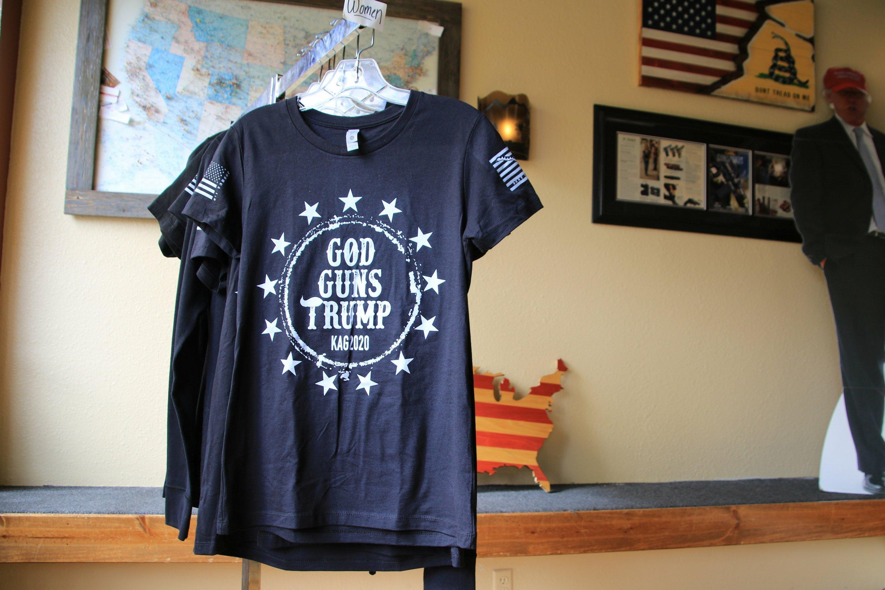 """Ein T-Shirt mit der Aufschrift """"God, Guns, Trump"""" hängt an einem Haken."""