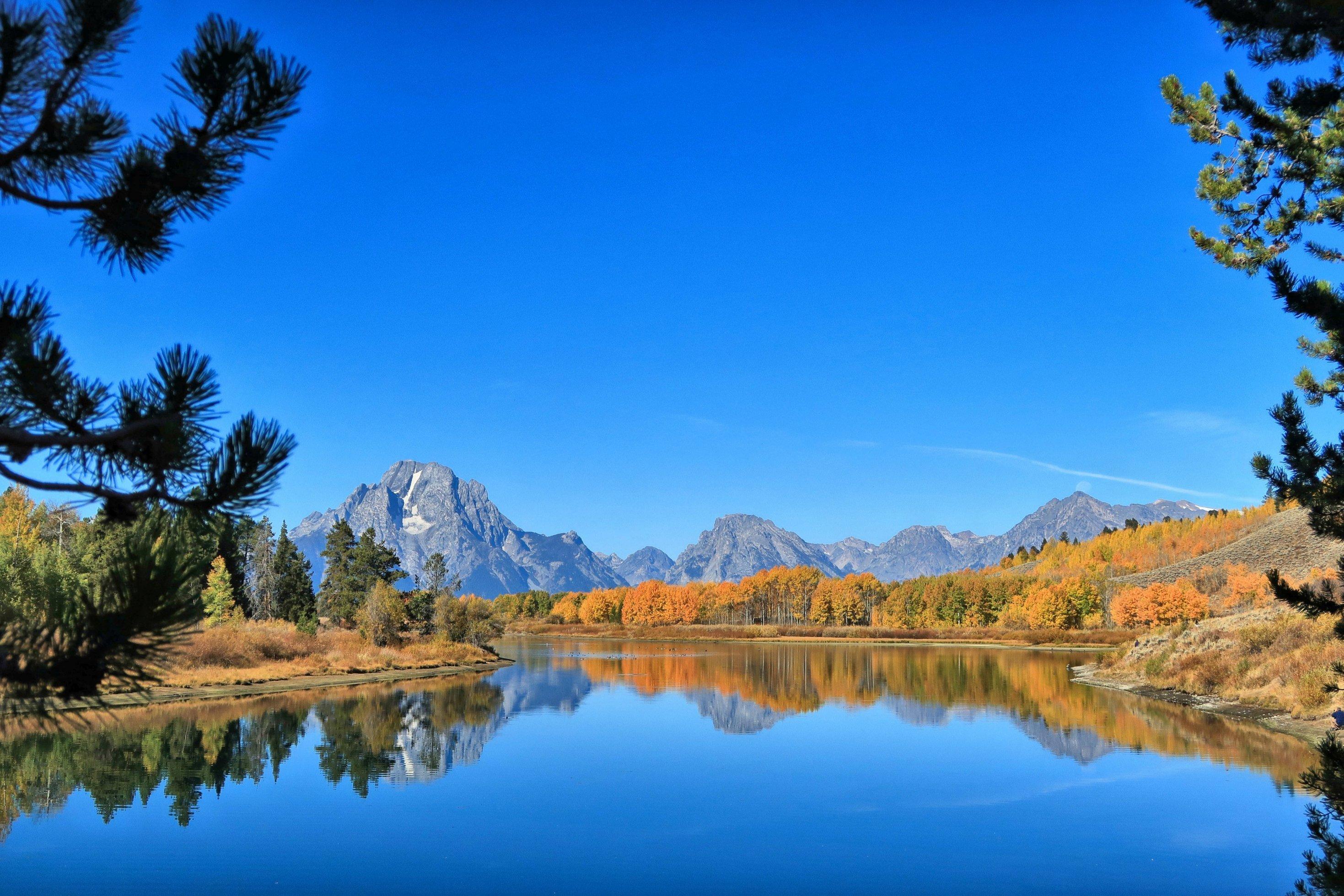Ein See, im Hintergrund Berge vor blauem Himmel